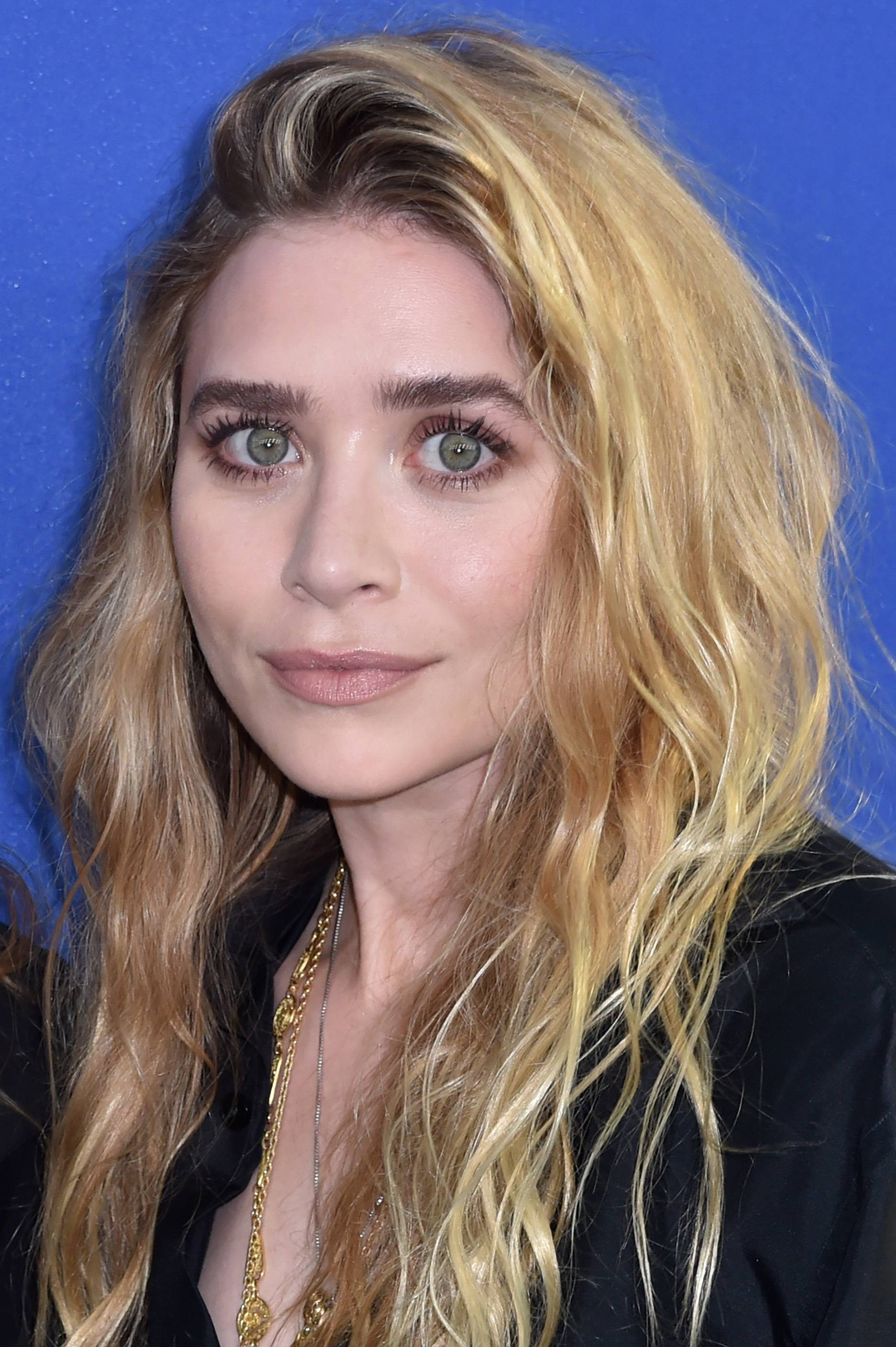 hairstyles for fine curly hair: ashley olsen with long wavy blonde beach hair pushed over to one side