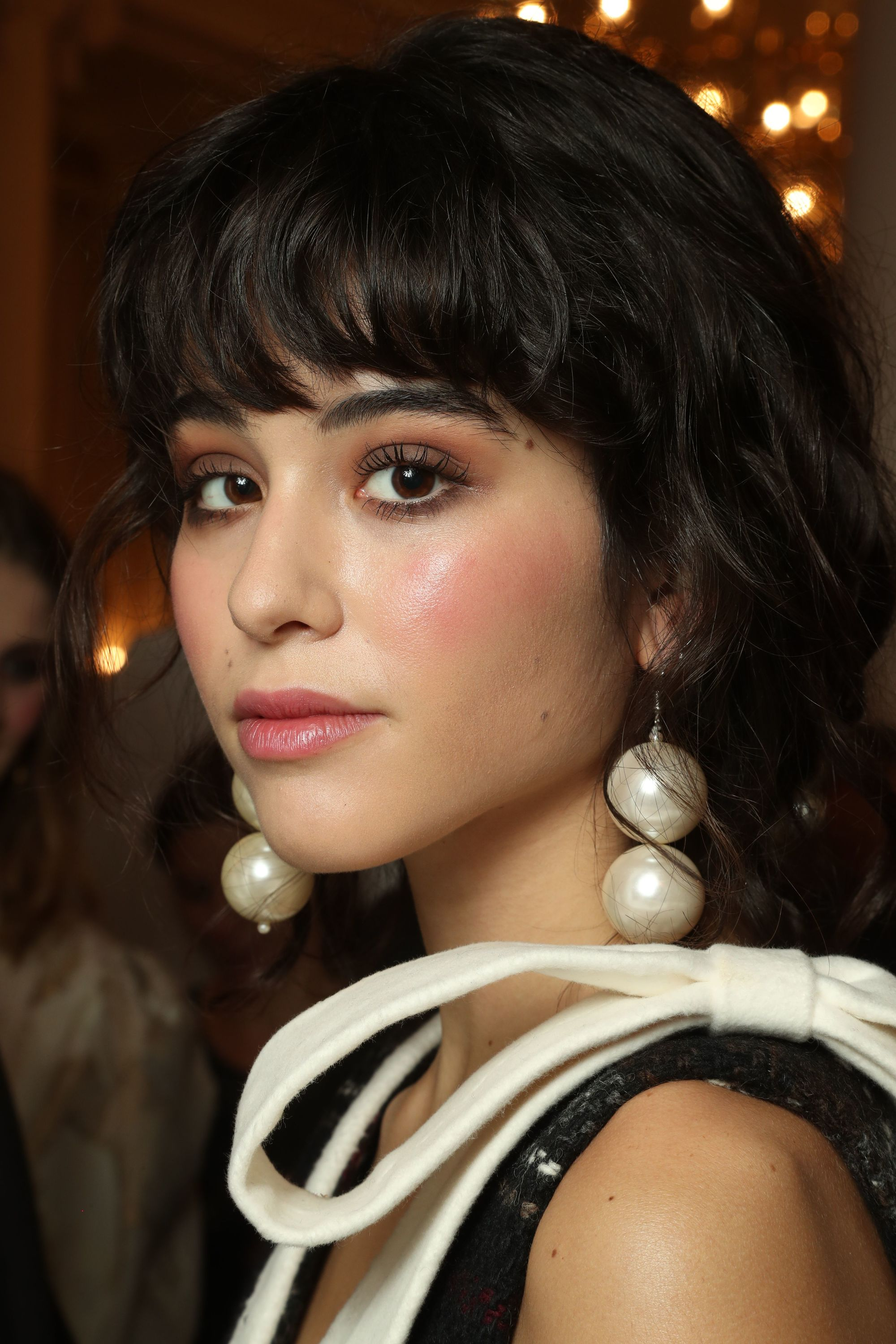 Haircuts for thick hair: Close-up backstage image of a model with dark brunette bowl cut hair with oversized pearl earrings.