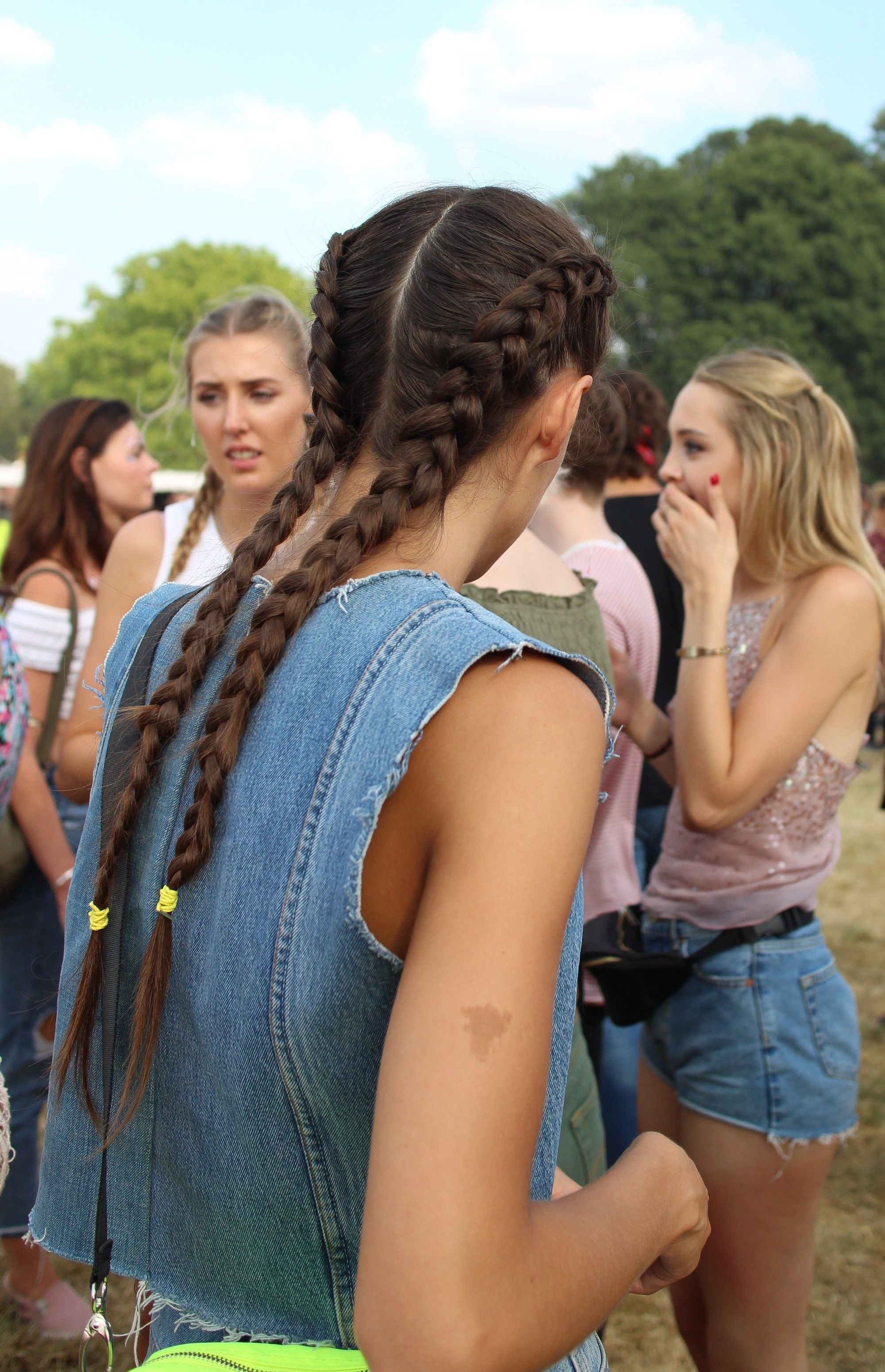 Photo from Lovebox festival 2018 of a woman with long brown hair in boxr braids wearing a denim waistcoat.