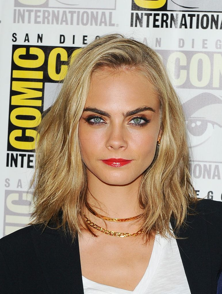 hairstyles for fine curly hair: cara delevingne at comic con with blonde shoulder length wavy lob hair