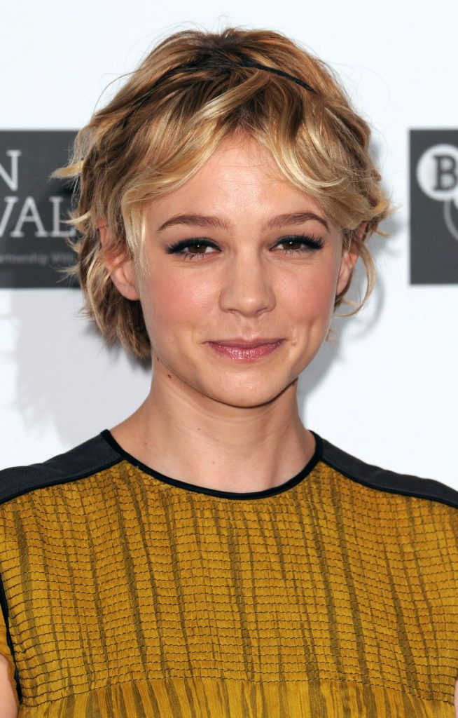 hairstyles for fine curly hair: actress carey mulligan with short curly bob hair with a thin black headband