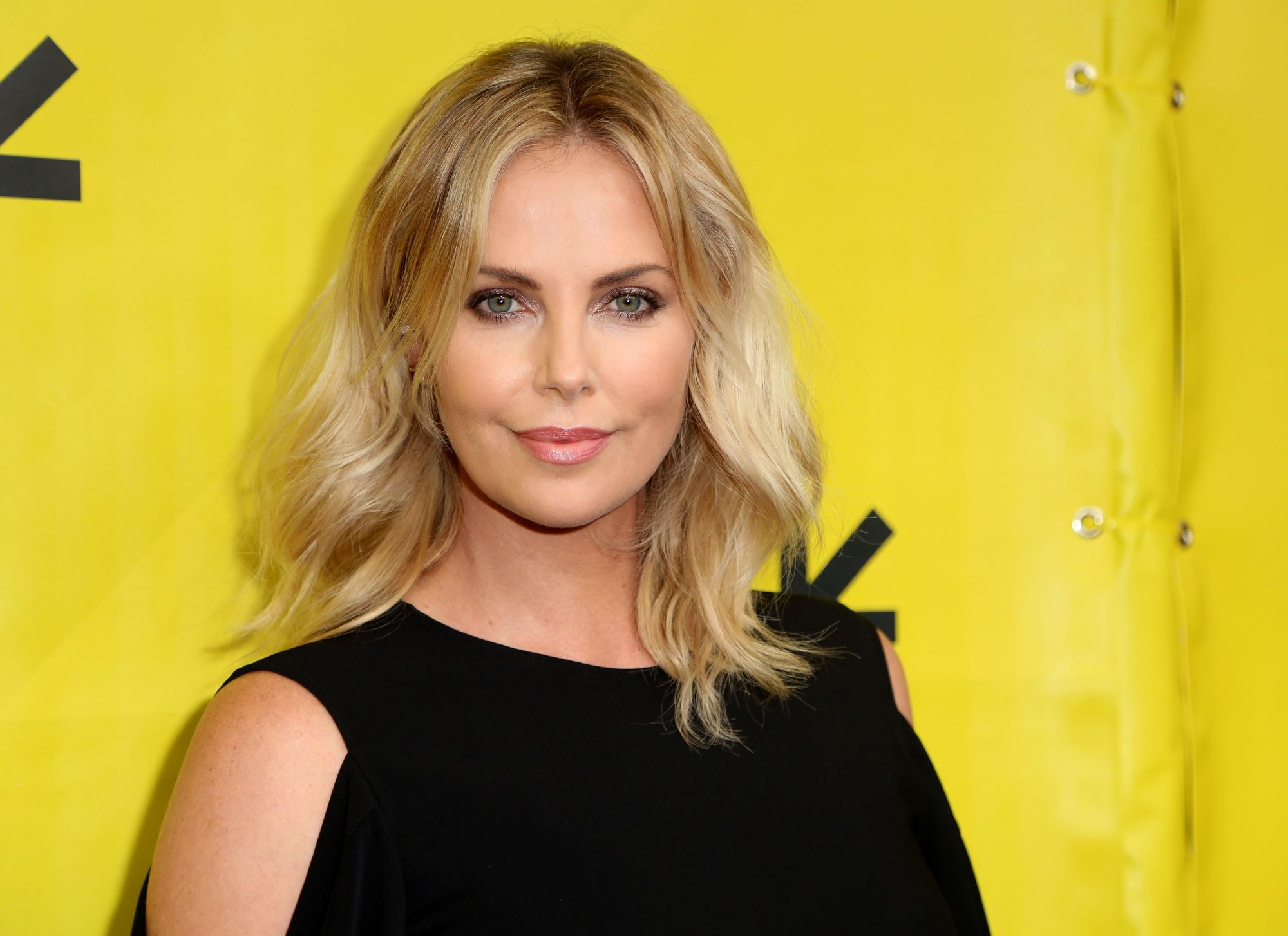 hairstyles for fine curly hair: charlize theron with shoulder length voluminous blonde curls with a centre parting