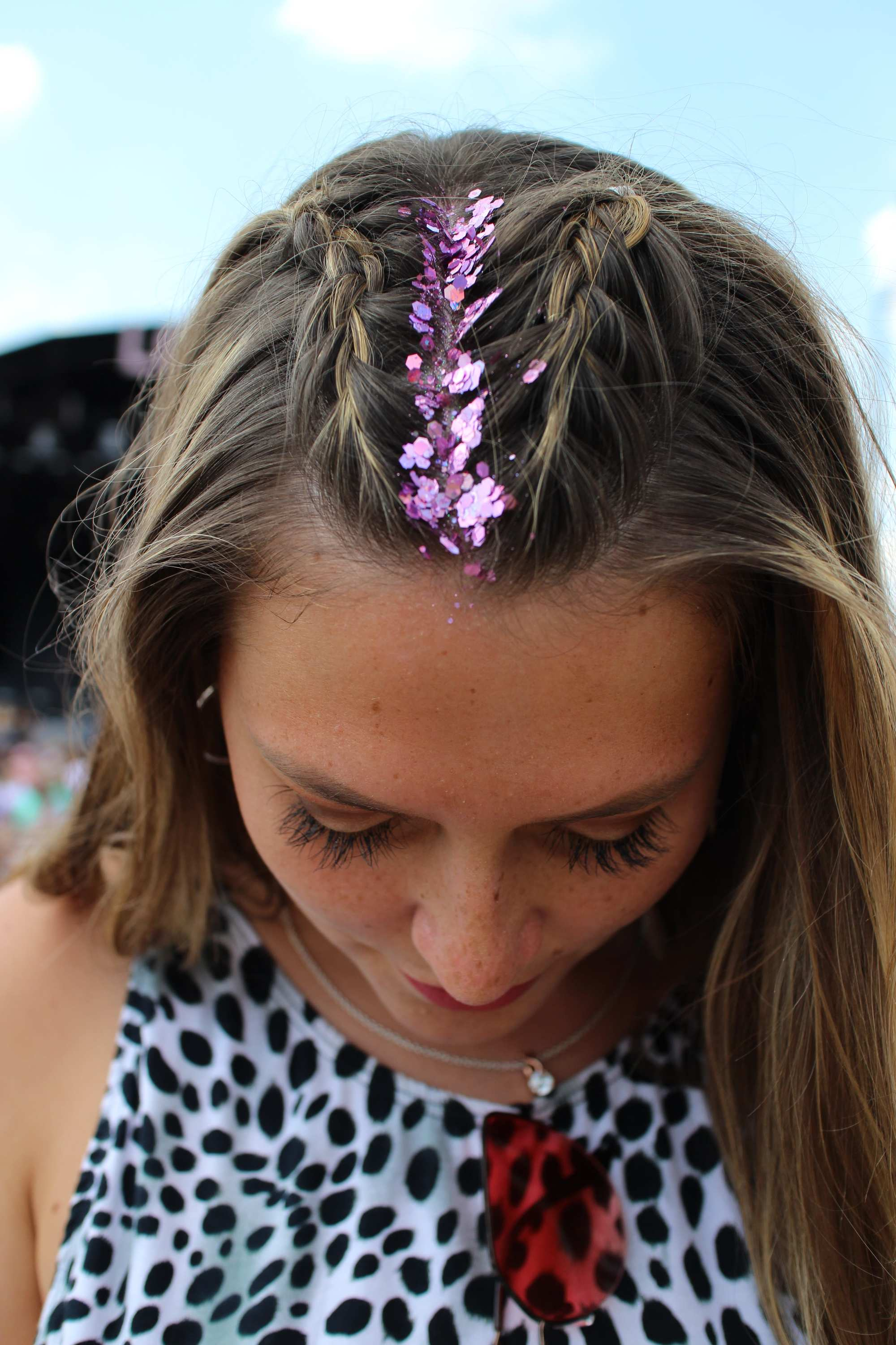 Close-up shot of a woman with dark blonde hair with chunky purple glitter roots and two unicorn braids with her hair down and straight, wearing an animal print top