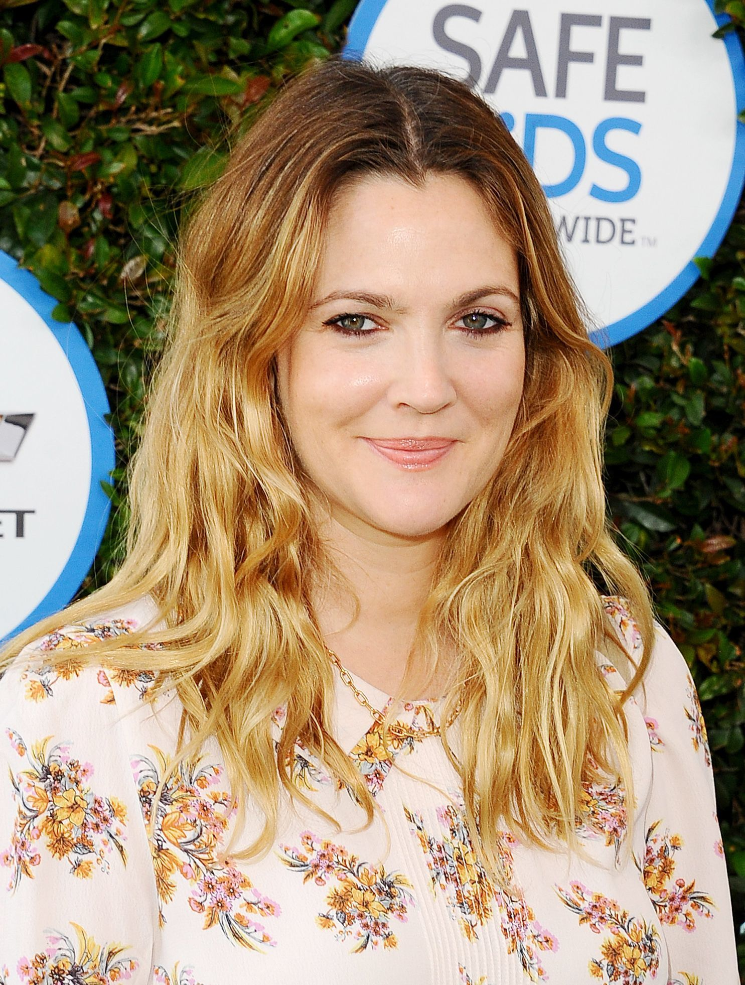 hairstyles for fine curly hair: drew barrymore with warm golden blonde wavy shoulder length hair with short split bangs