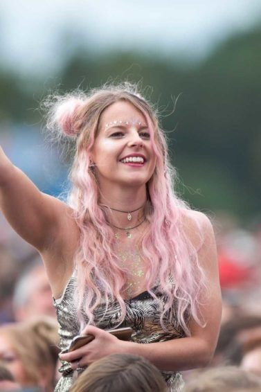 Woman in the crowd at a festival with long wavy pink hair in half up space buns with hidden braids and hair rings
