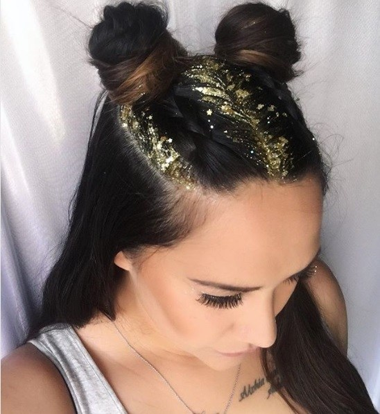 Close-up of a woman with dark brown hair in half-up space buns with gold glitter roots