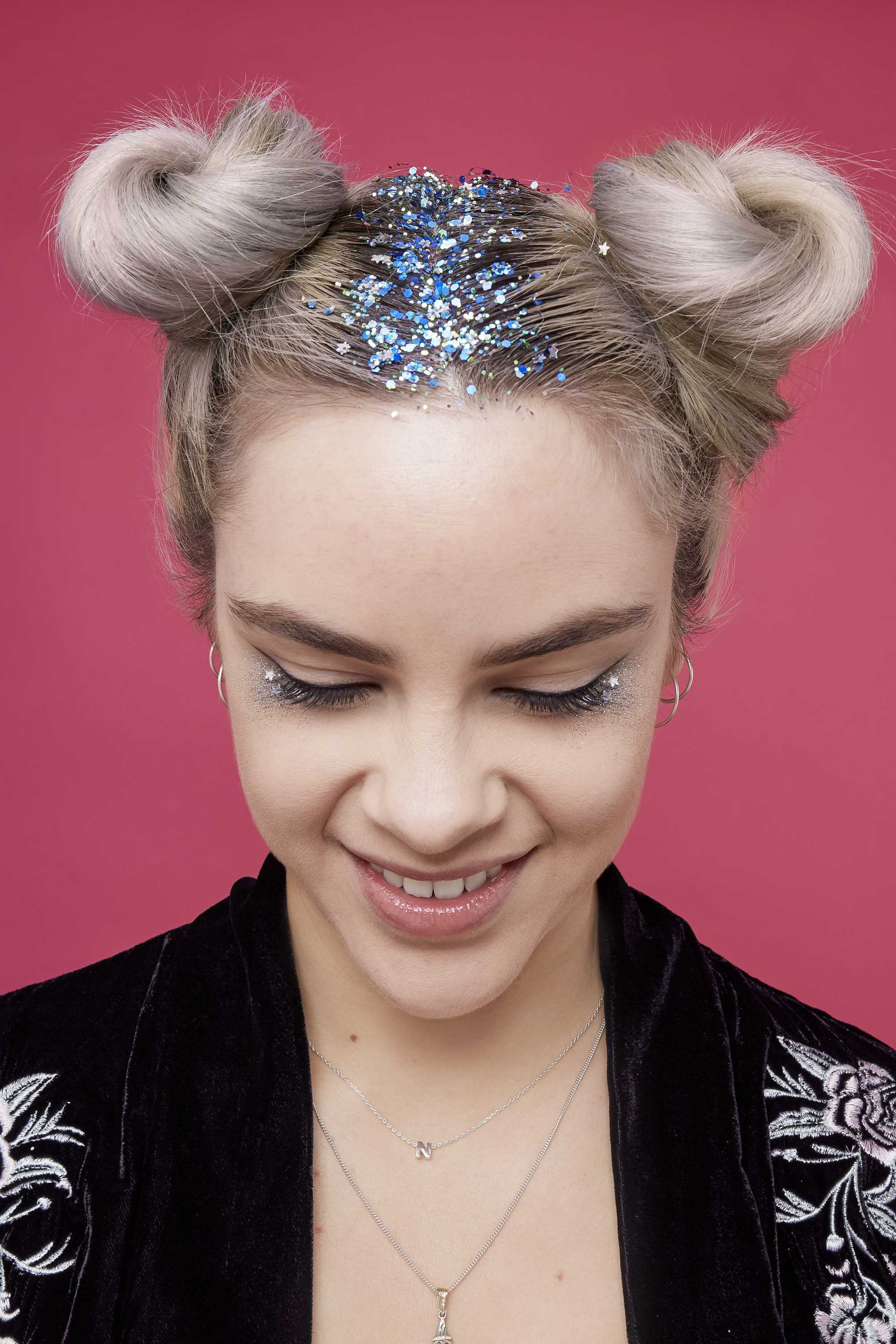Blonde woman with space buns and blue glitter roots, wearing a black embroidered velvet jacket and standing against a pink background