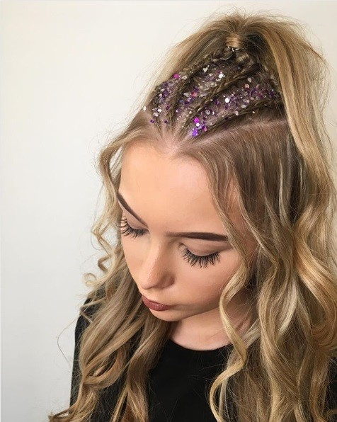 Photo of a woman with blonde curly hair with a half-up cornrow braided ponytail with pink and purple glitter roots