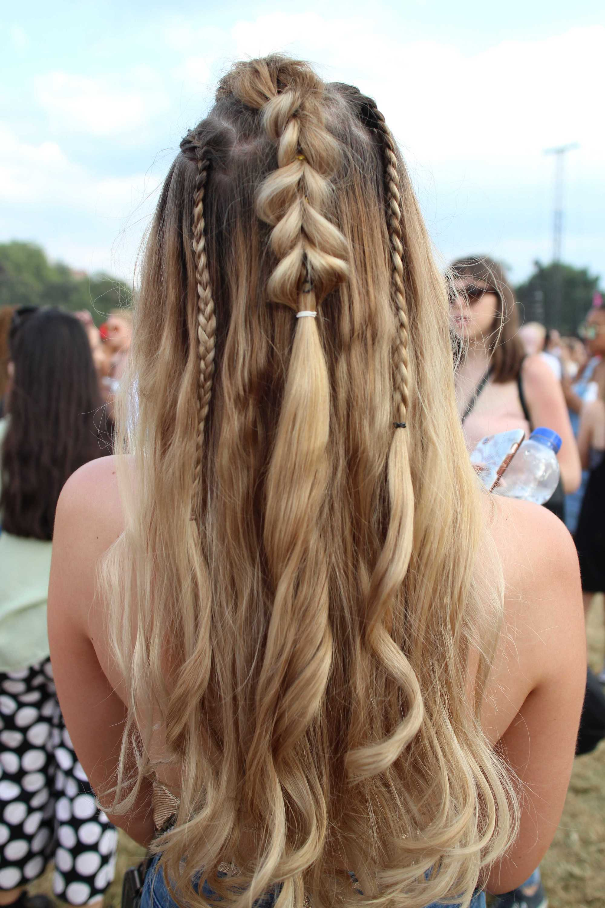 back view of a woman at lovebox festival with dirty blonde long hair in a half up pull through braid with mini accent braids added in