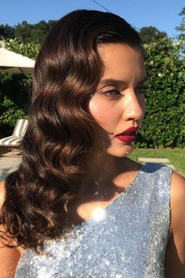 Vintage hairstyles for curly hair: brunette woman with sideswept vintage hollywood waves wearing a silver sequin dress