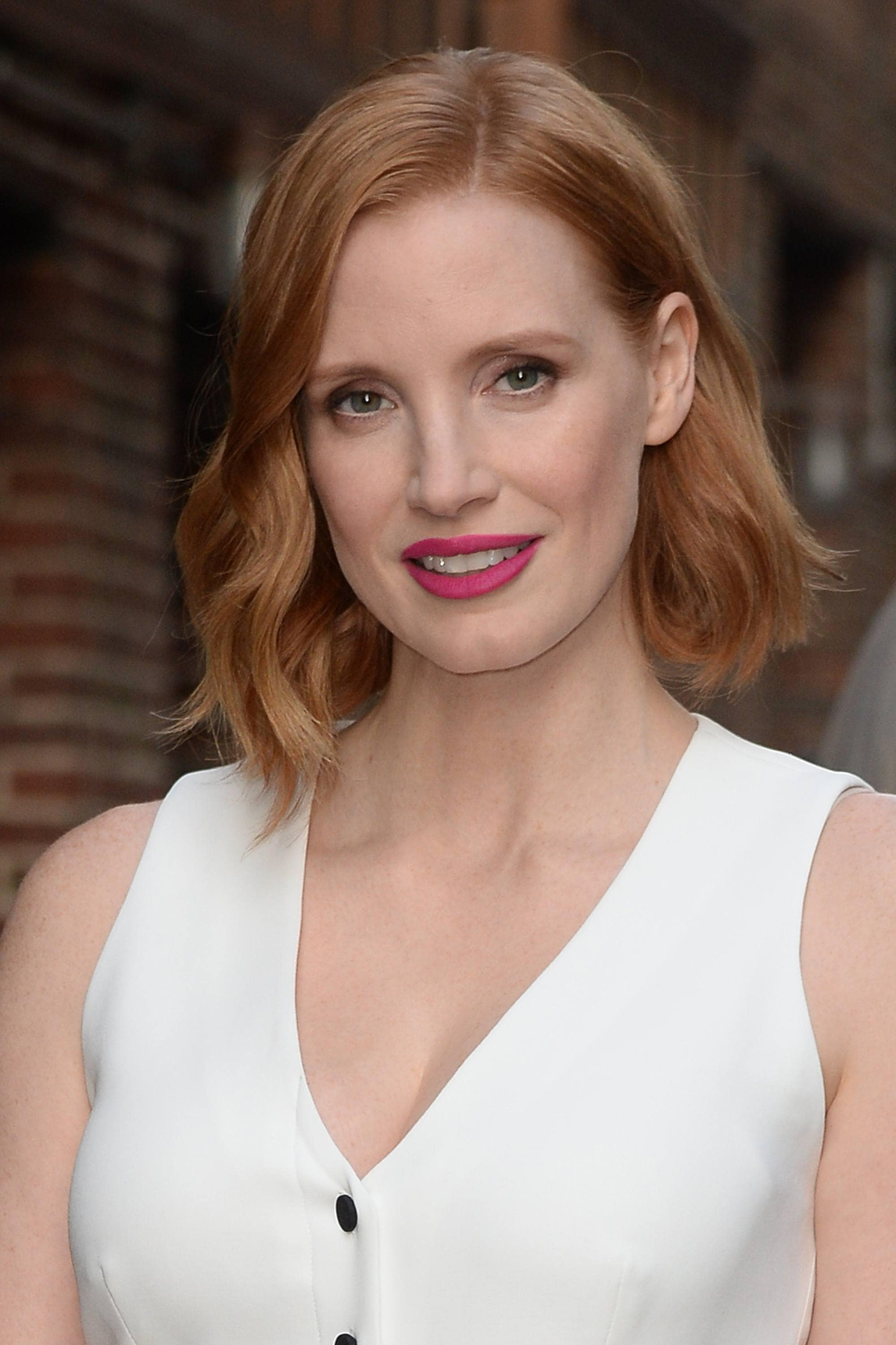hairstyles for fine curly hair: jessica chastain with her red hair in an Asymmetric bob style with long side longer than the other
