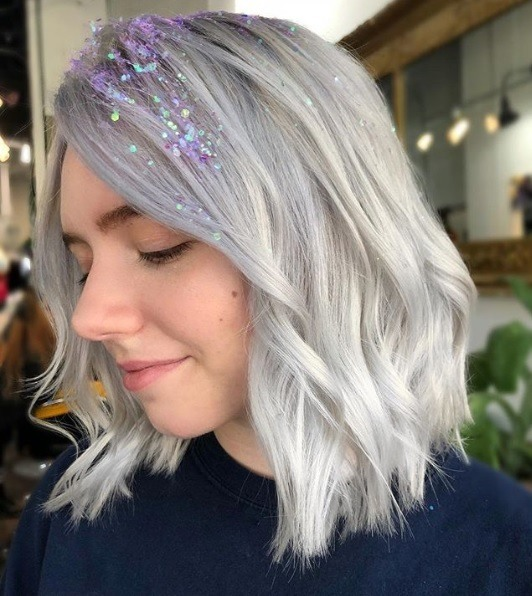Woman with lob length curled silver blonde hair with purple lilac glitter roots in her fringe