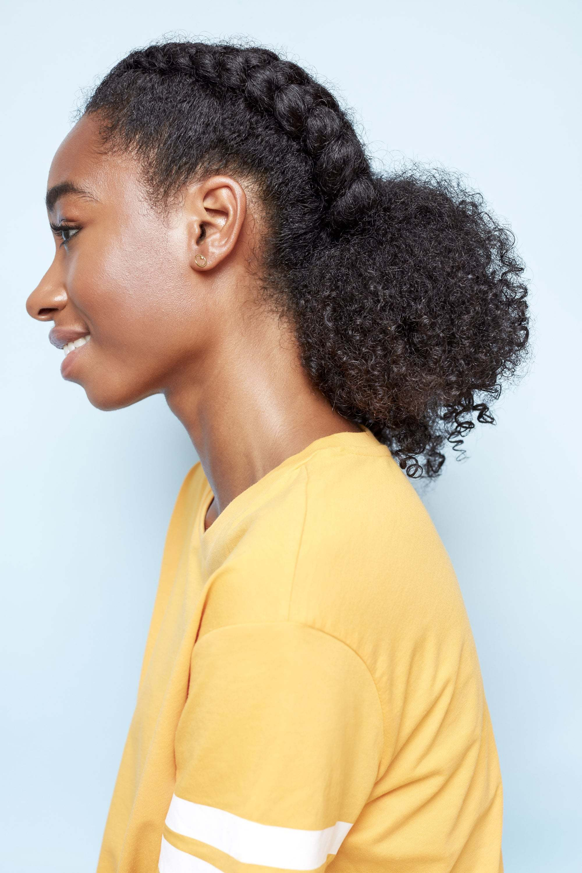 hairstyles for black women: close up shot of a woman with a dark brown afro hair fashioned into a braided, low ponytail posing outside