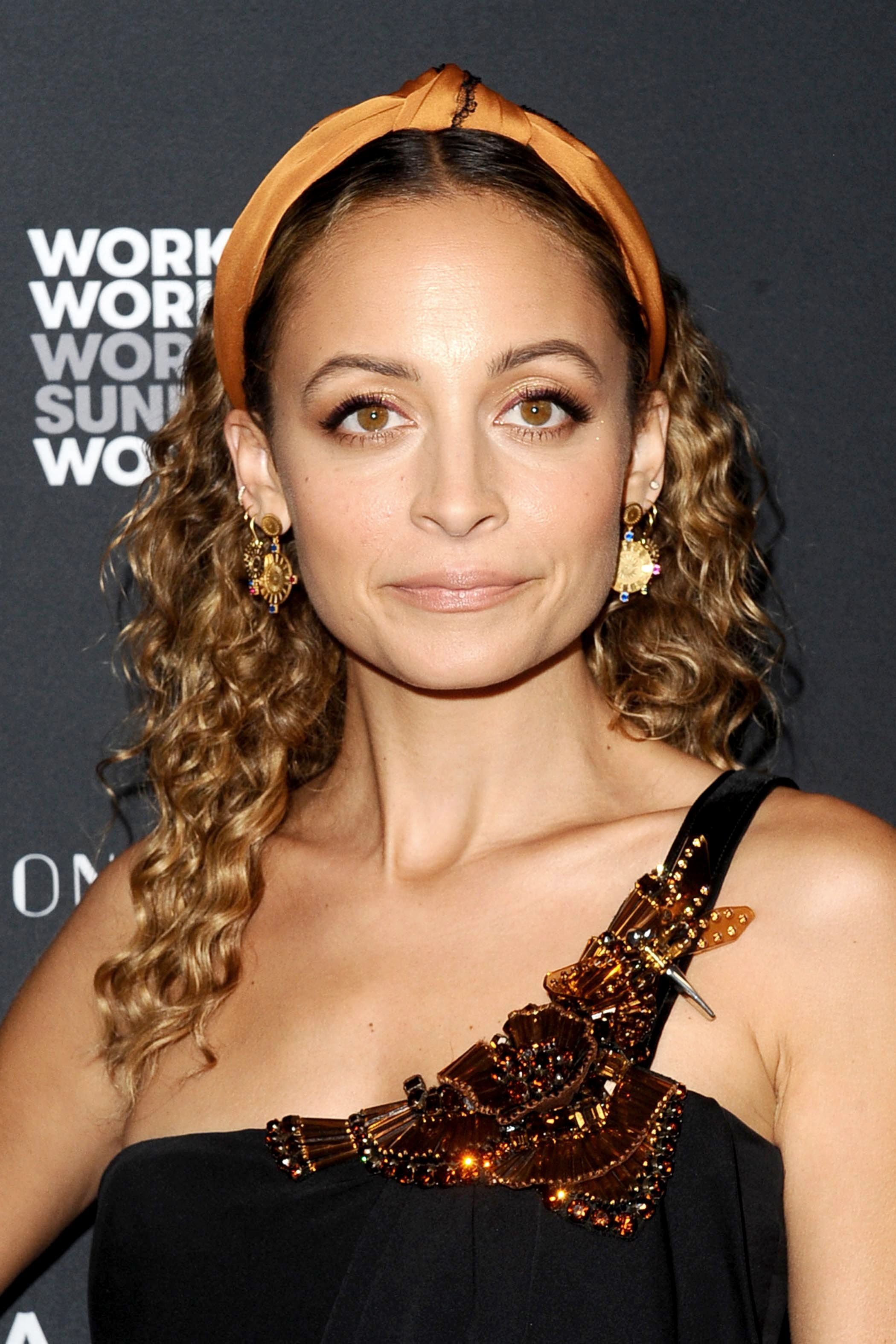 Headband and bandana hairstyles: Nicole Ritchie with golden brown curly medium length hair wearing a orange knotted headband.