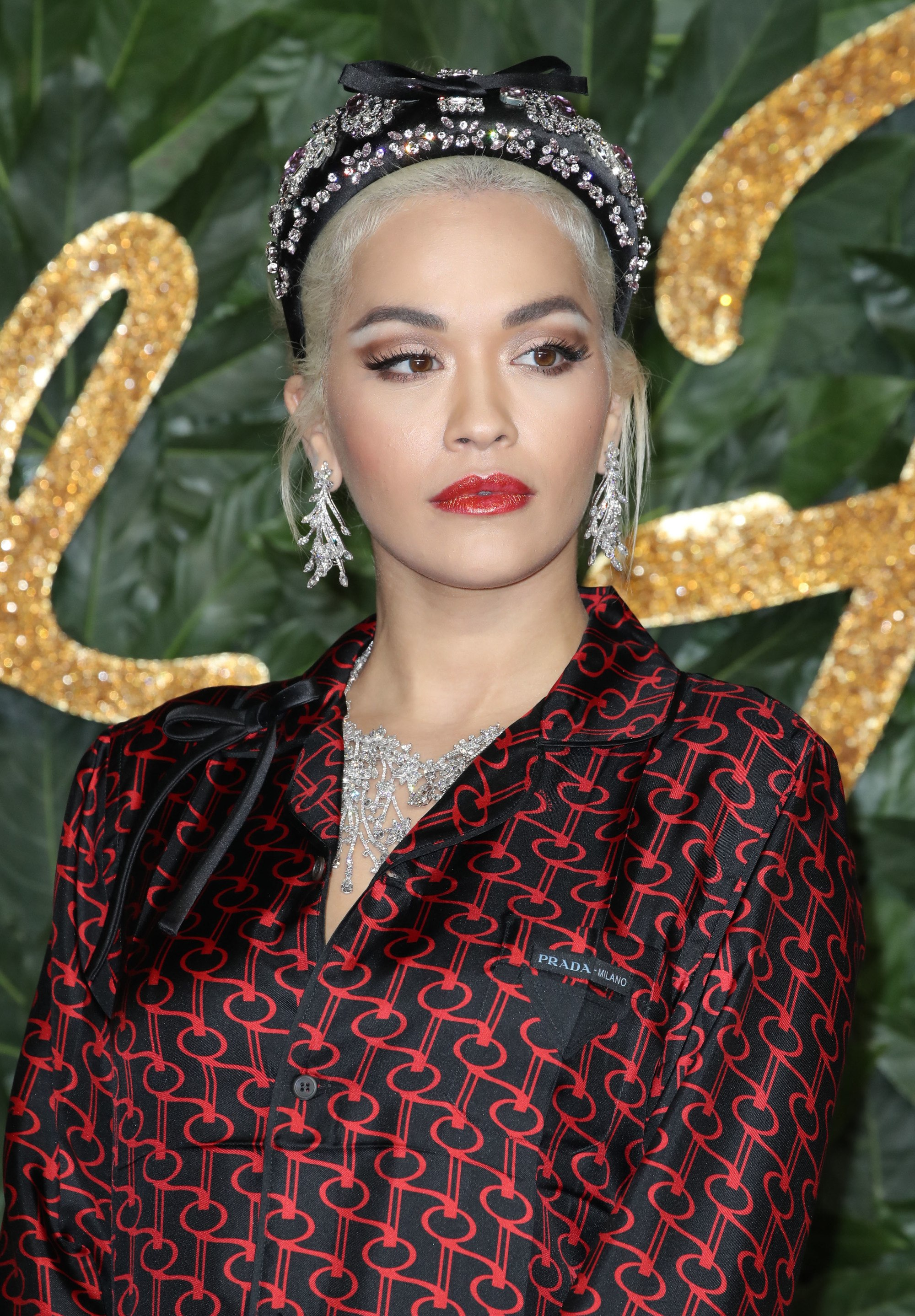 Headband and bandana hairstyles: Rita Ora with bleach blonde white hair in updo wearing a black jewelled headband with a bow and red pattern shirt.