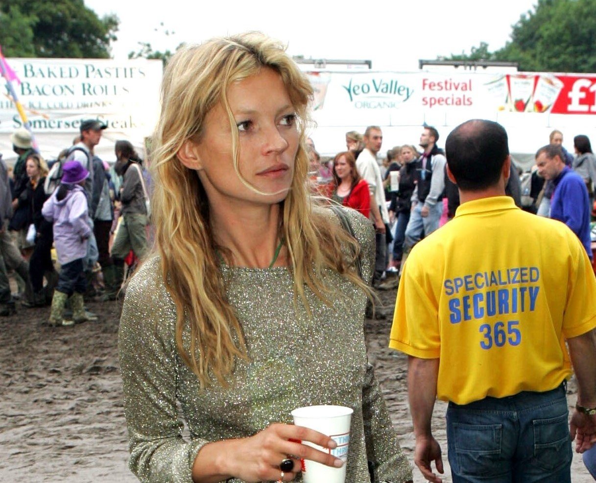 Close up crop of Kate Moss at Glastonbury festival in 2005 with dirty blonde messy hair in a half-up, half-down hairstyle.