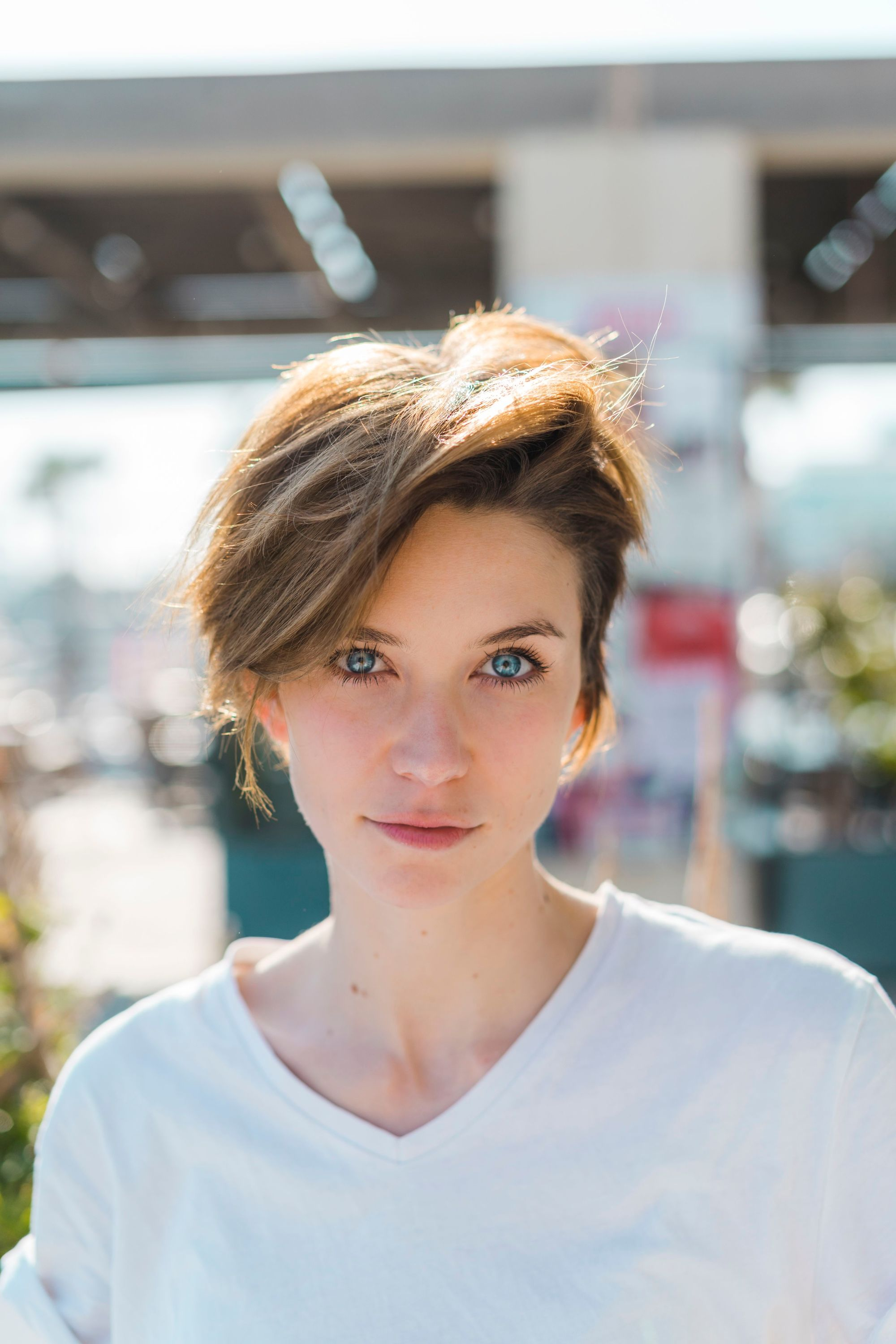 Haircuts for thick hair: Close up photo of a brunette woman with short pixie cut hair with sweeping layers