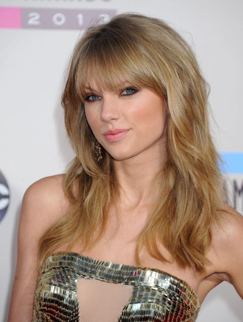 hairstyles for fine curly hair: taylor swift with long wavy blonde hair with a fringe