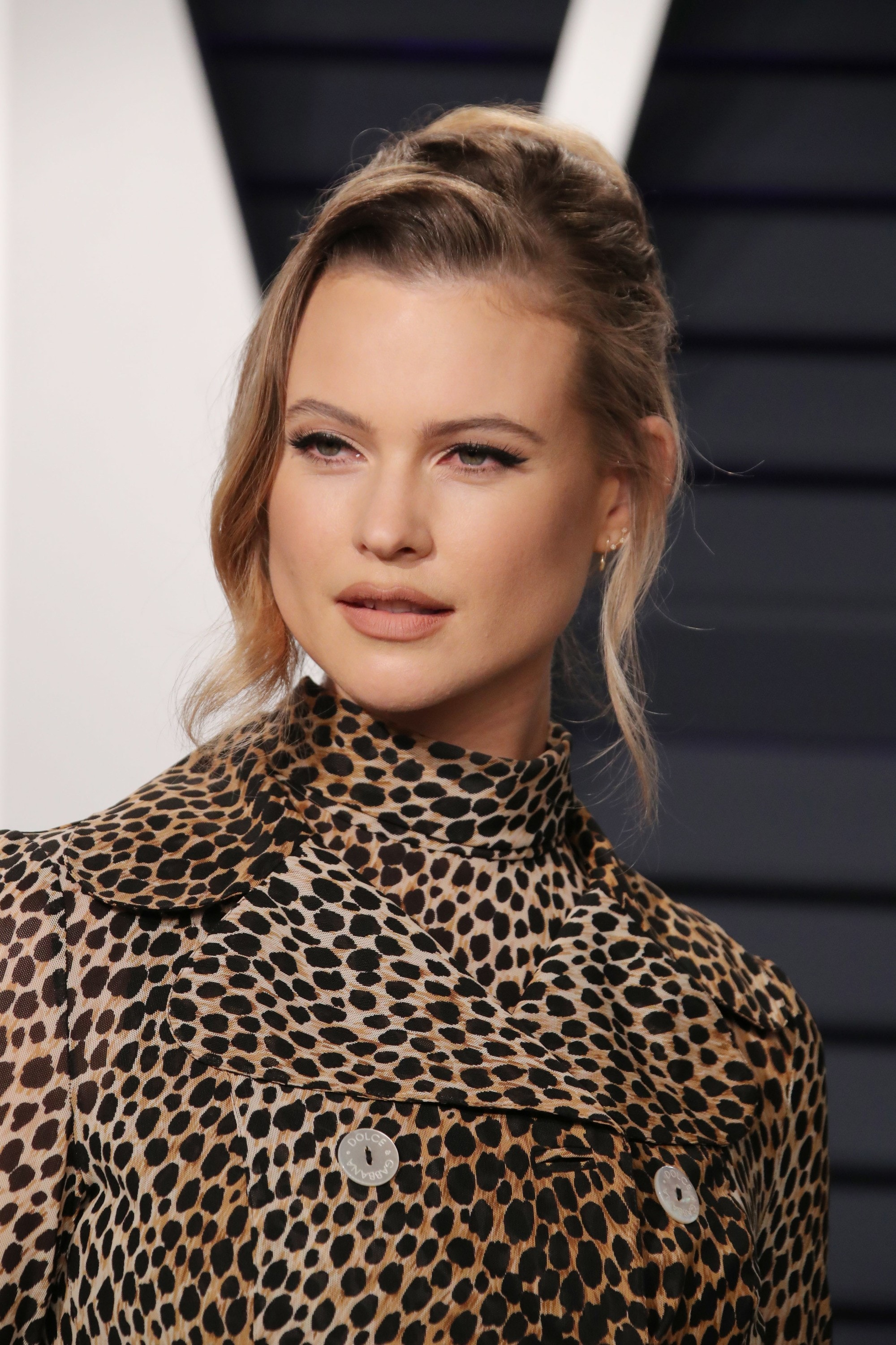 Behati Prinsloo with her ashy caramel blonde hair styled into a romantic updo, wearing leopard print on the red carpet