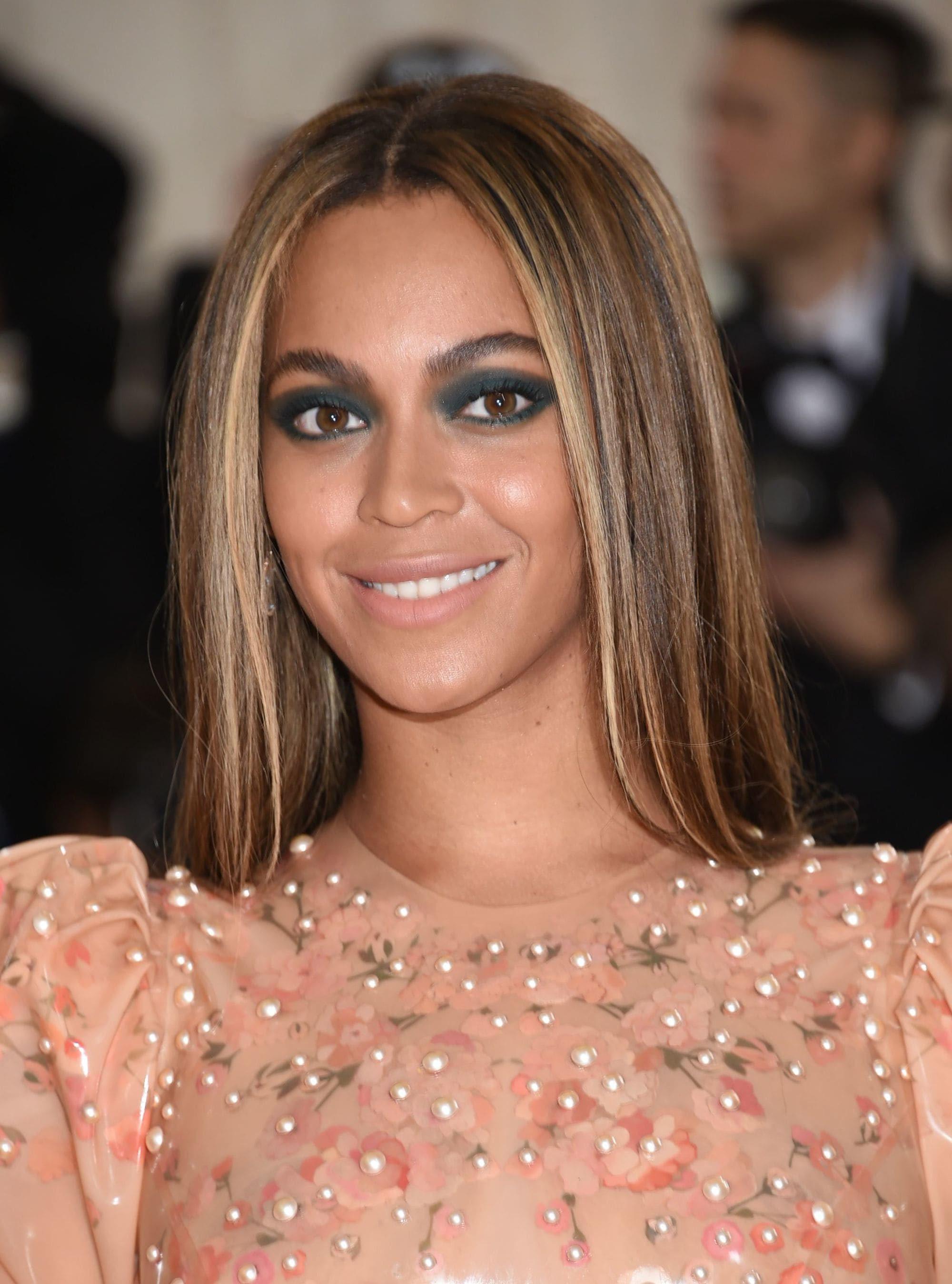 Beyonce with long straight caramel brown hair with blonde highlights, wearing rose gold dress on the red carpet