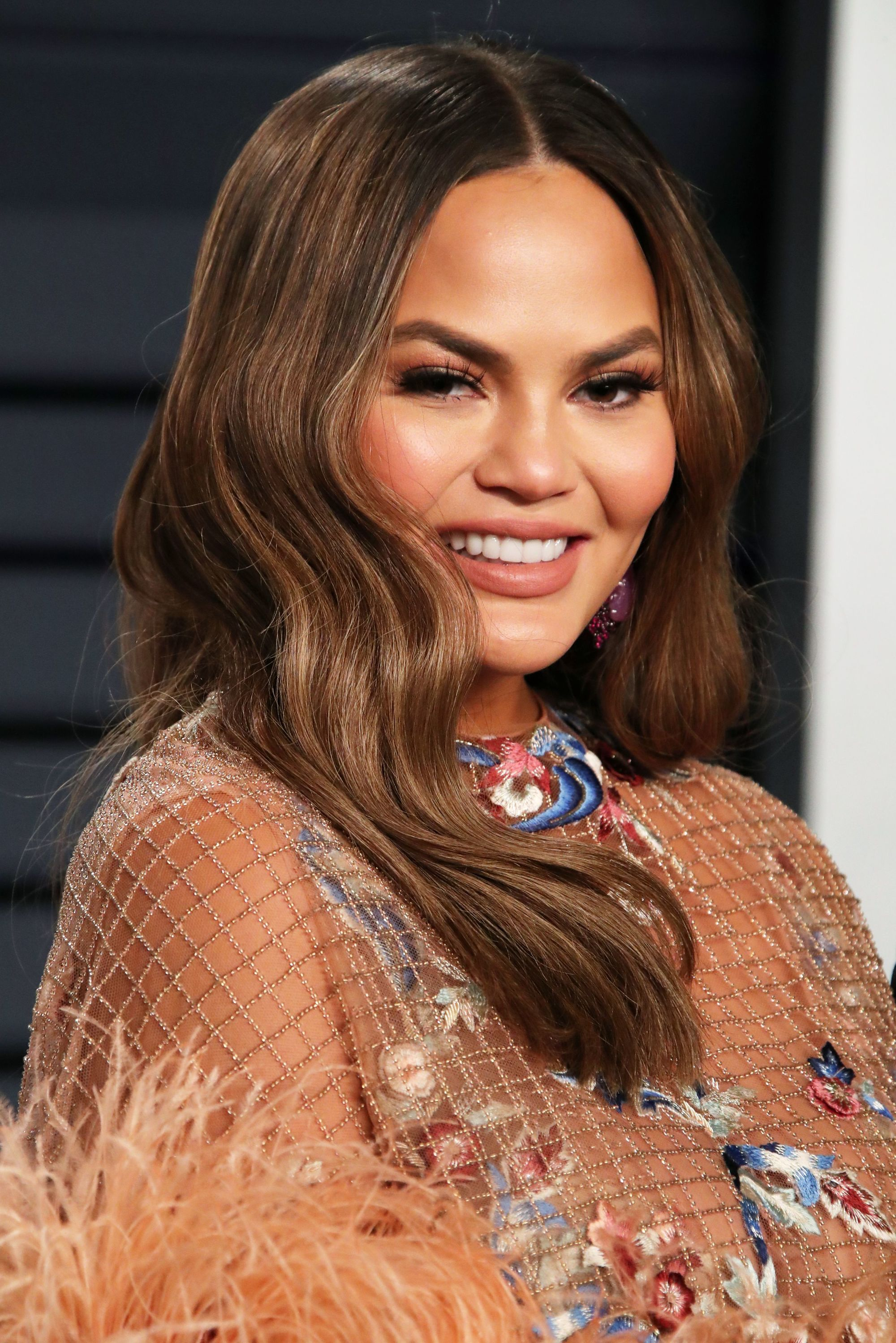 Chrissy Teigen with loose glamorous long wavy dark brown hair with subtle caramel highlights