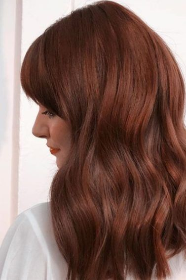 Cinnamon hair colour: Woman with medium length cinnamon red hair with bangs styled into a smooth blowdry hairstyle