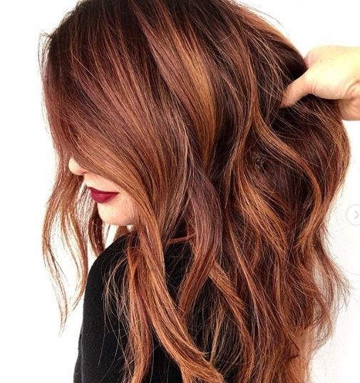 CInnamon hair colour ideas: Woman with dark brown hair with cinnamon red melt, with her hair styled into loose waves