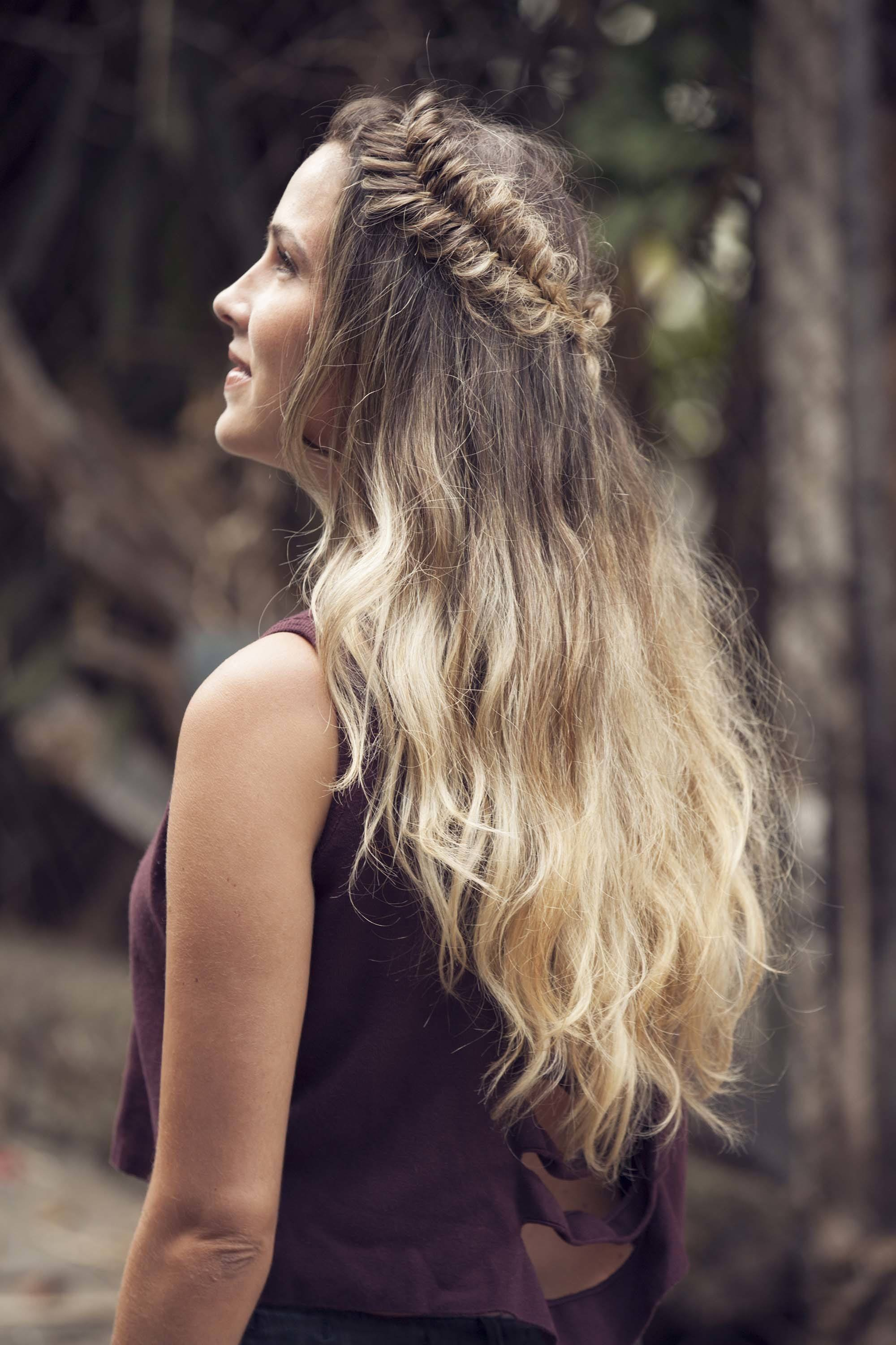 Crown hair: Close up shot of a woman with long dark brown hair with blonde ombre styled into a messy half-up, half-down crown, wearing a red top and posing outside