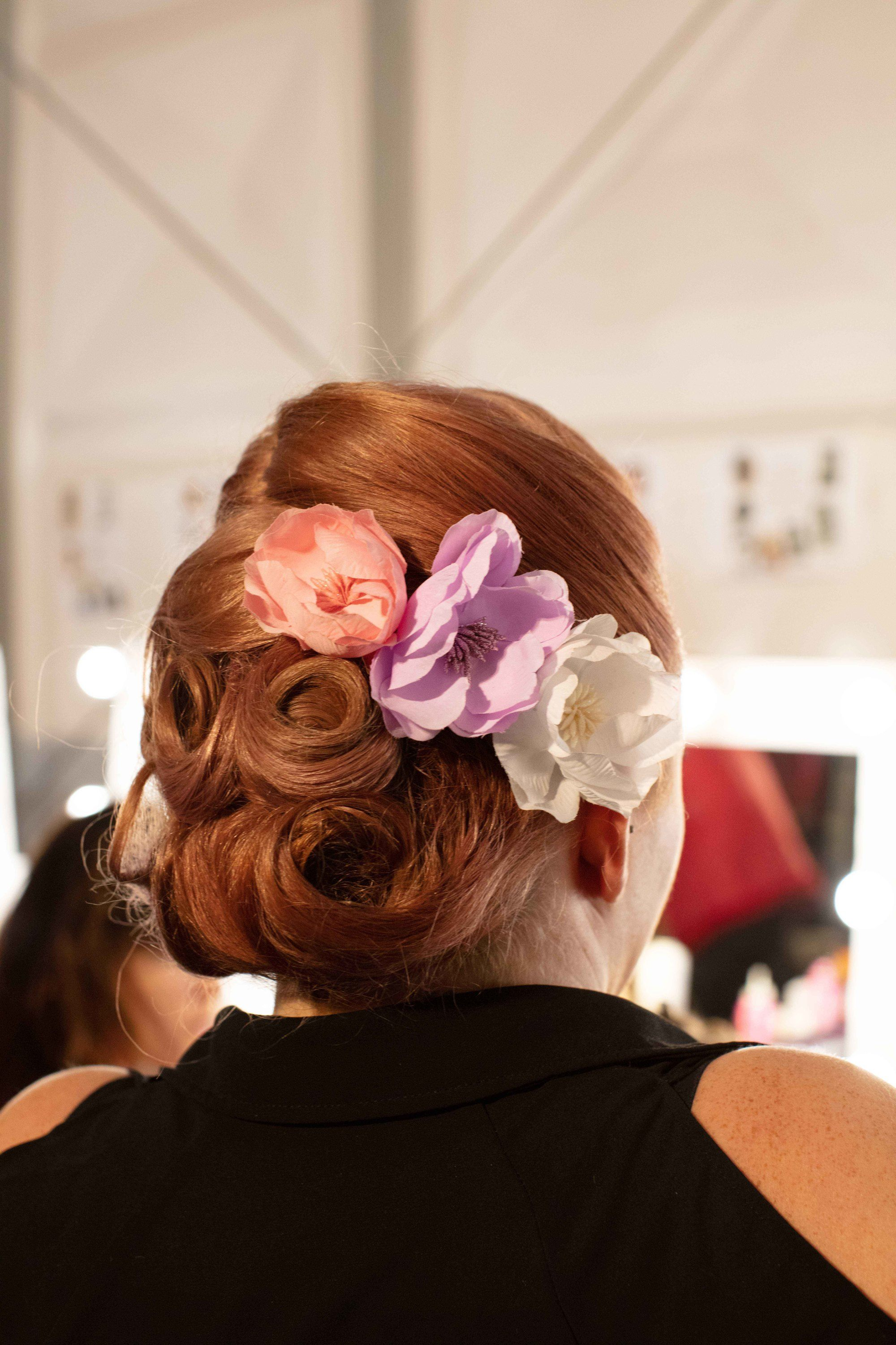 1940s hairstyles: Back shot of a woman ginger red hair styled into pin curled updo with flowers in it