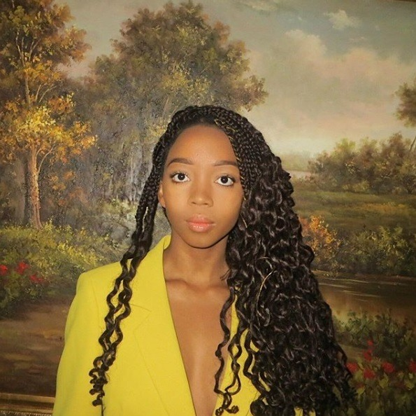 Long box braids: Woman with long curly dark brown box braids, worn over to side and wearing a yellow blazer