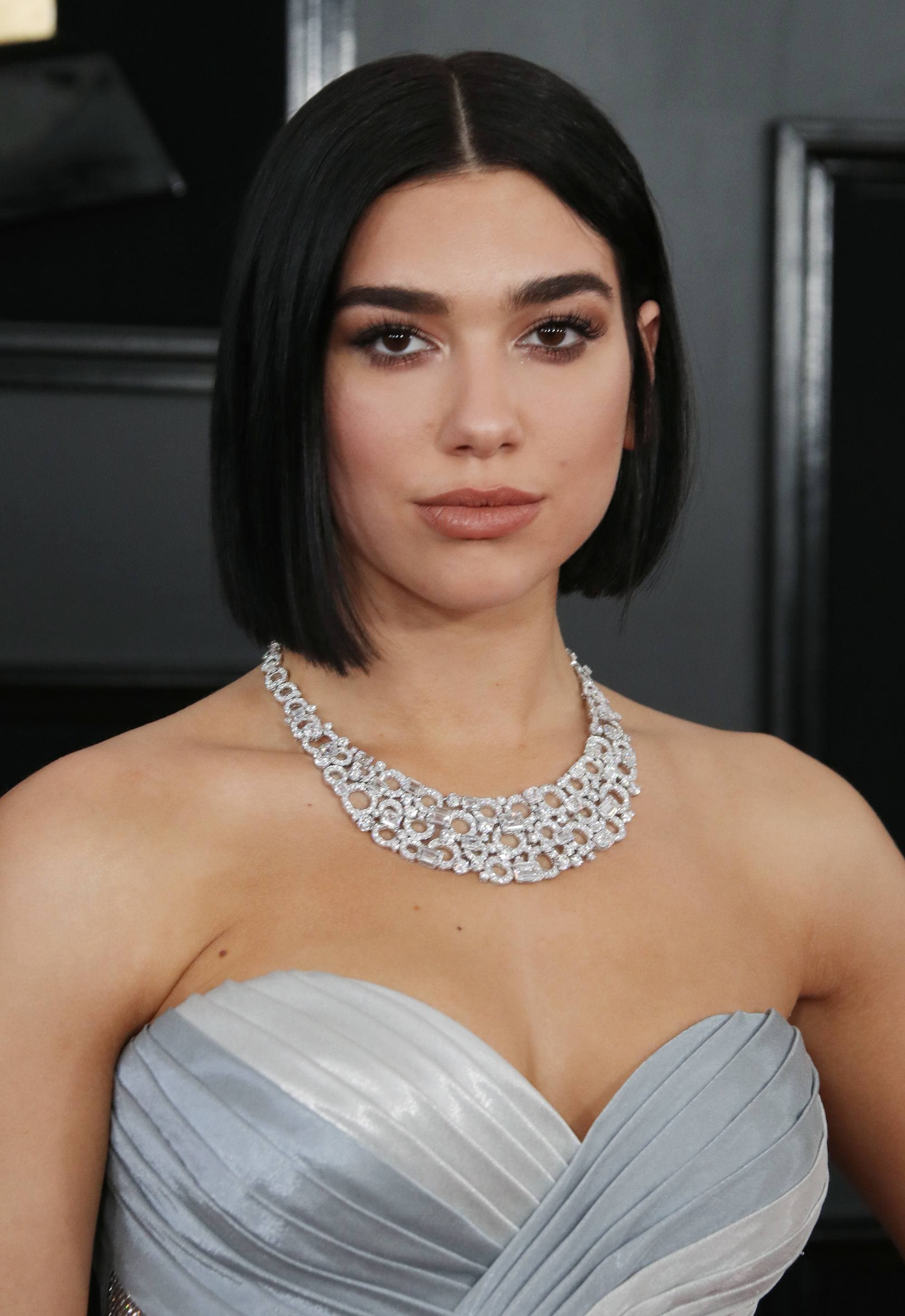 Red carpet hairstyles: Dua Lipa with dark brown straight blunt bob on red carpet wearing a strapless pale blue dress and diamond necklace.