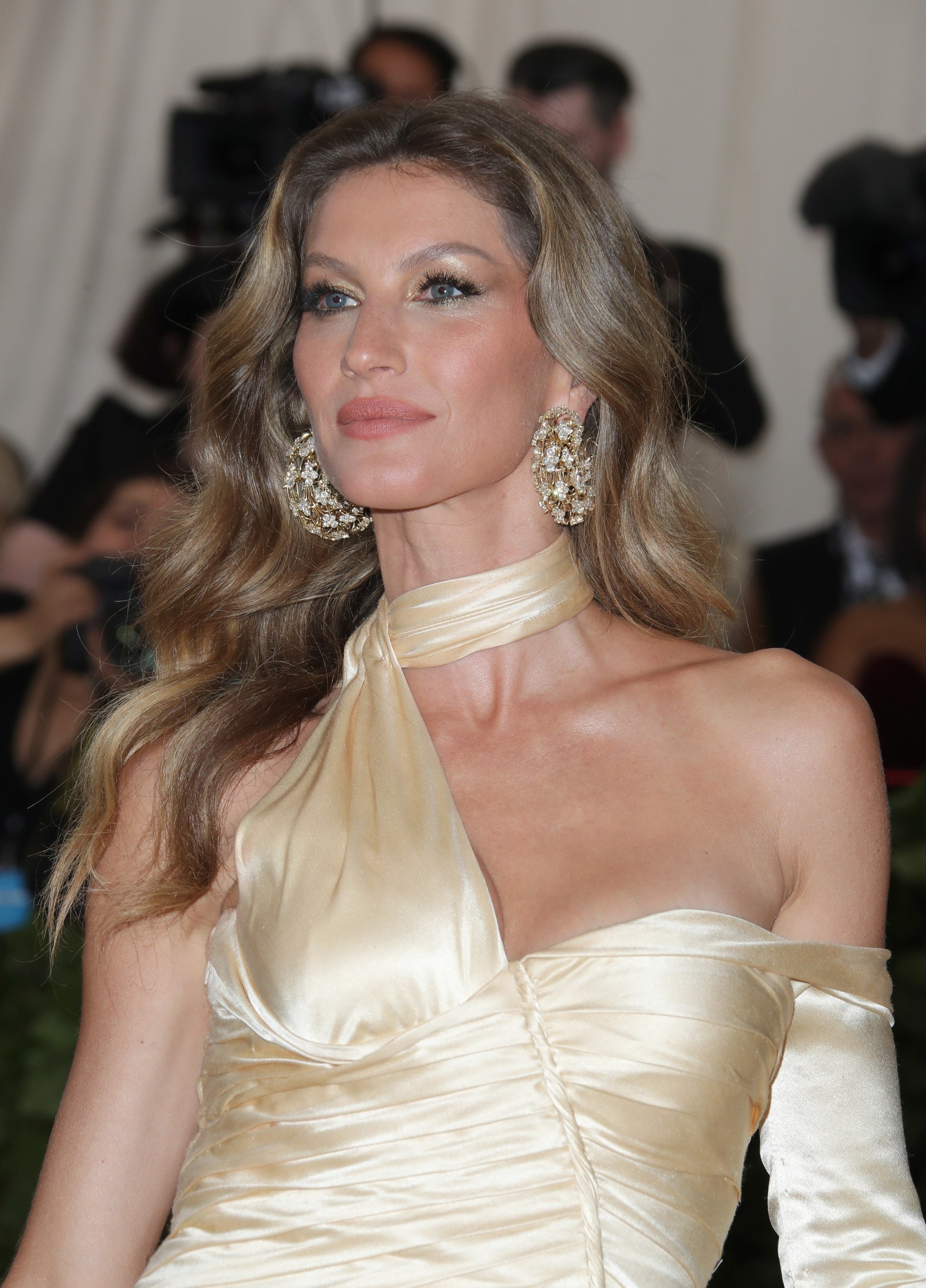 Gisele Bundchen with long chestnut brown hair with caramel highlights in it, wearing satin dress on the red carpet