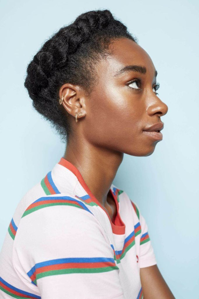Crown hair: Close up shot of a woman with her dark natural hair styled into a crown braid