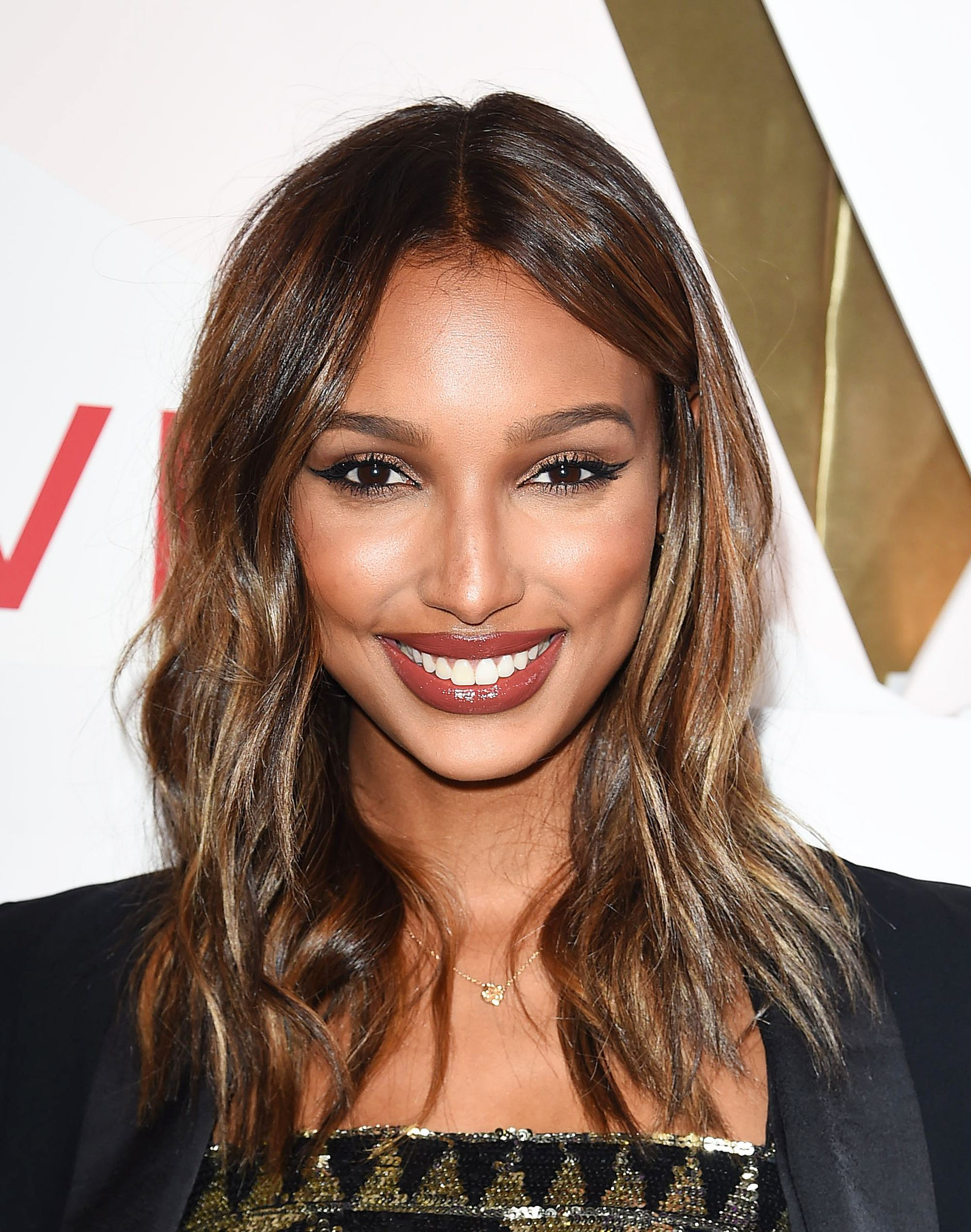 Jasmine Tookes with shoulder-length dark hair with caramel highlights in it on the red carpet