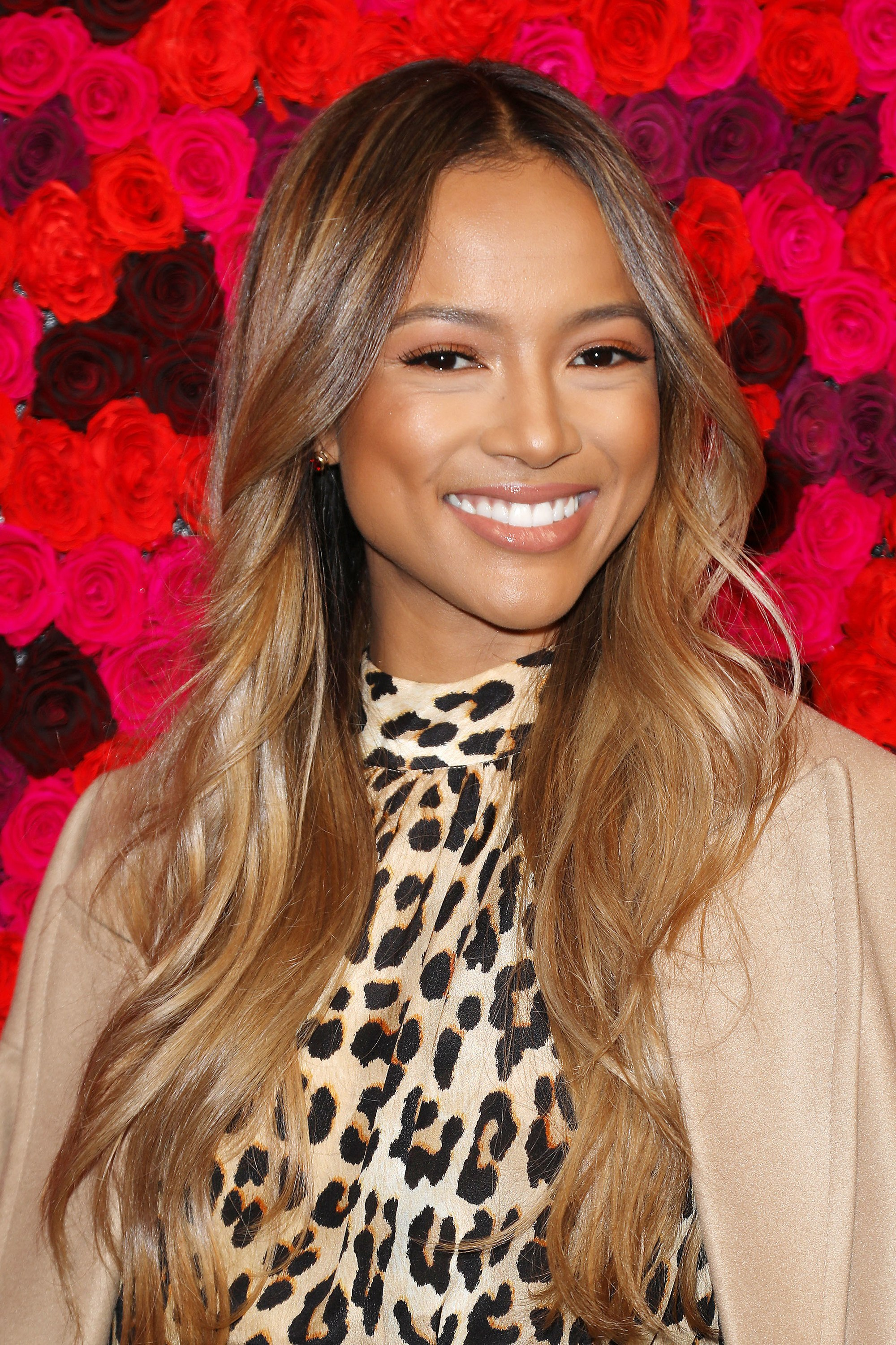 Karrueche Tran on the red carpet with long wavy dark brown and honey caramel hair, wearing leopard print with nude jacket on the red carpet