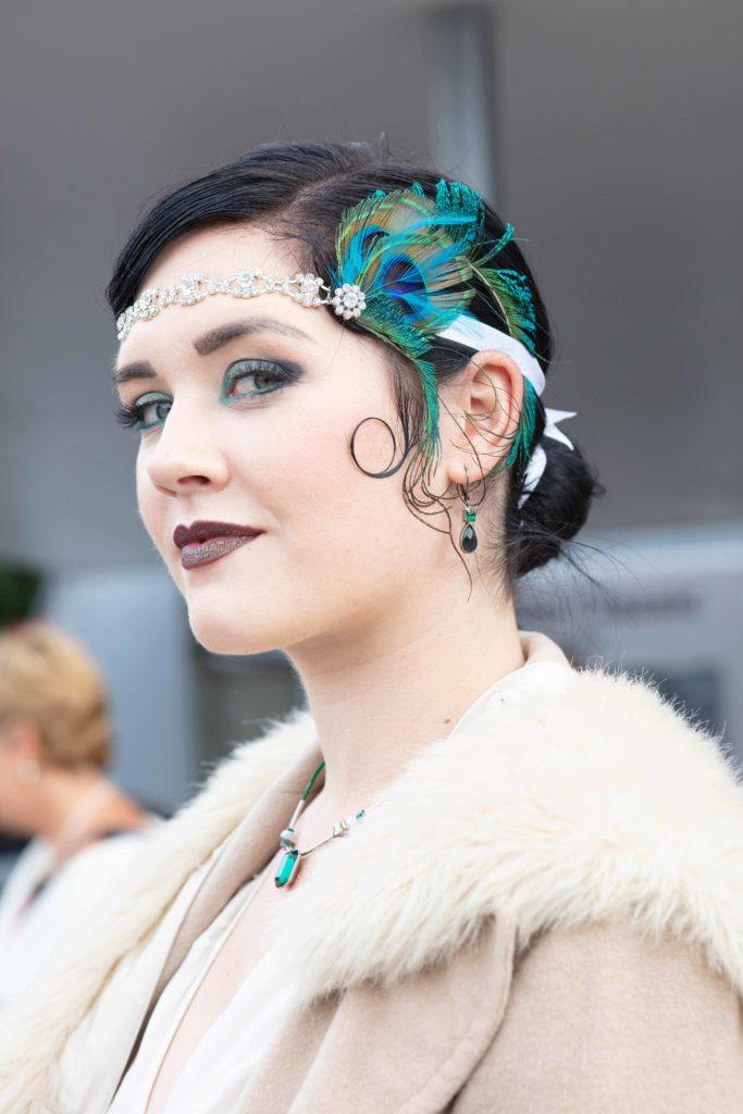 Vintage short hair: Close up shot of a woman with dark short hair styled into a low flapper style bun, with headband and peacock feather at Goodwood festival