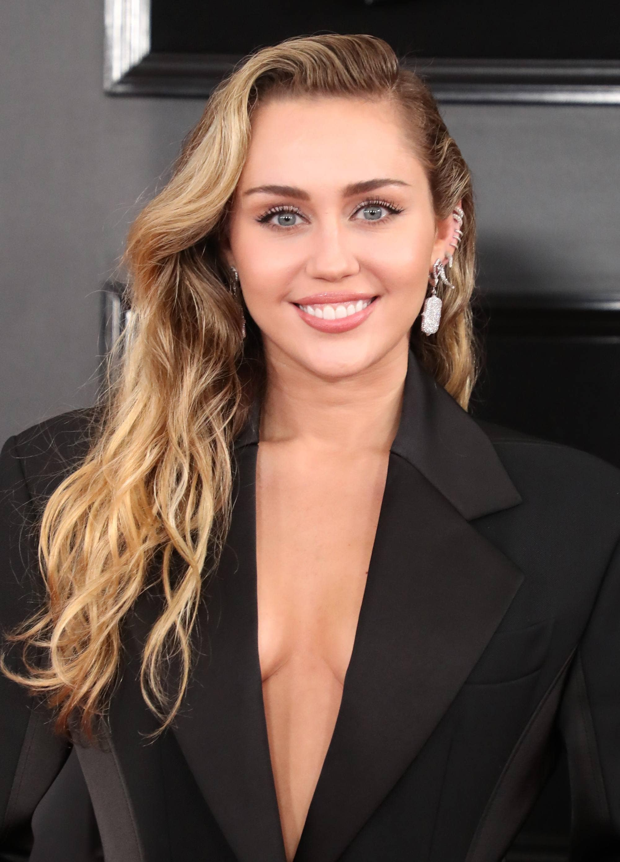 Red carpet hairstyles: Miley Cyrus with softly swept waves on her blonde hair with a black blazer jacket.