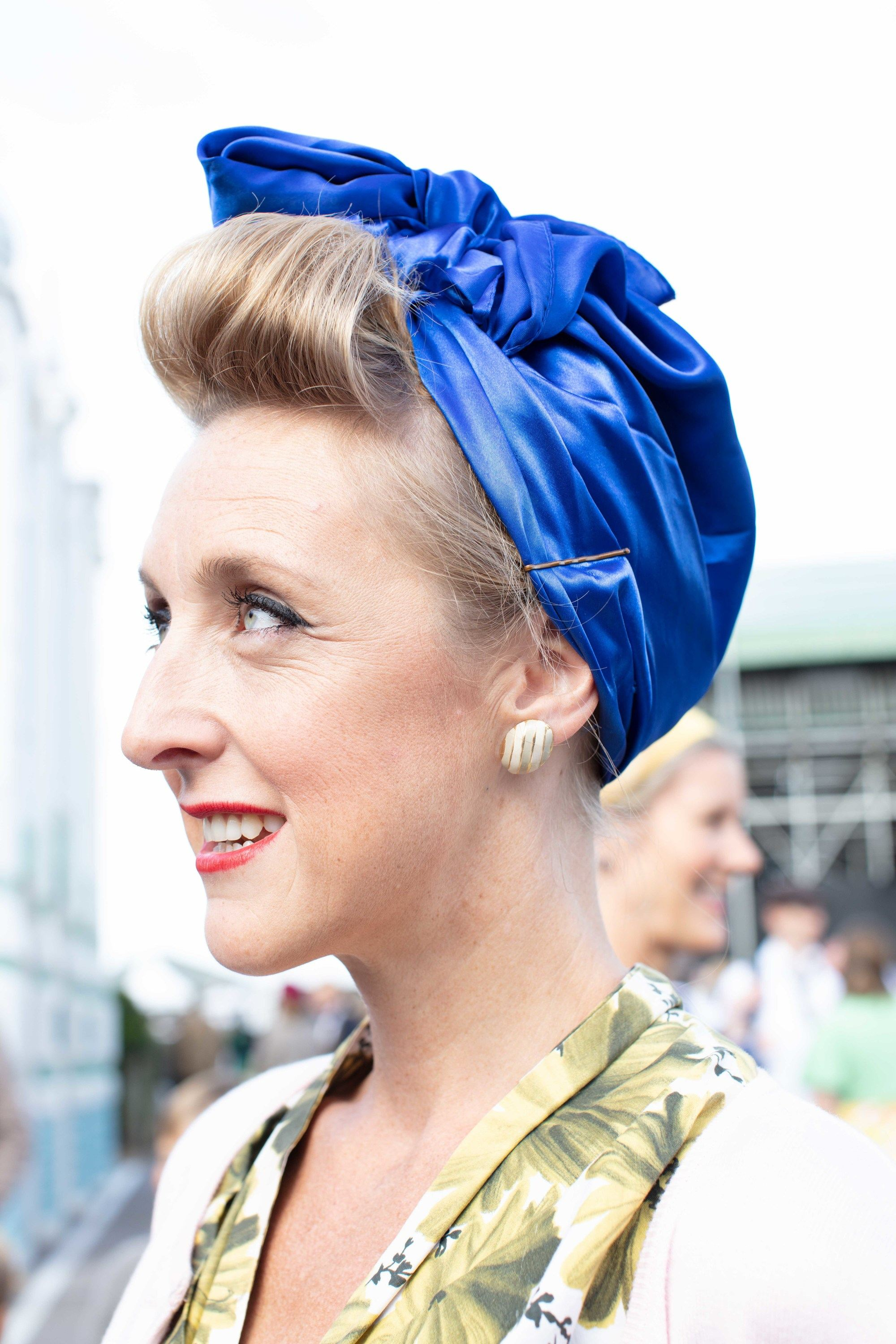 '50s hairstyles: Close up shot of a woman with golden blonde hair styled into a roll with a silk headwrap around it