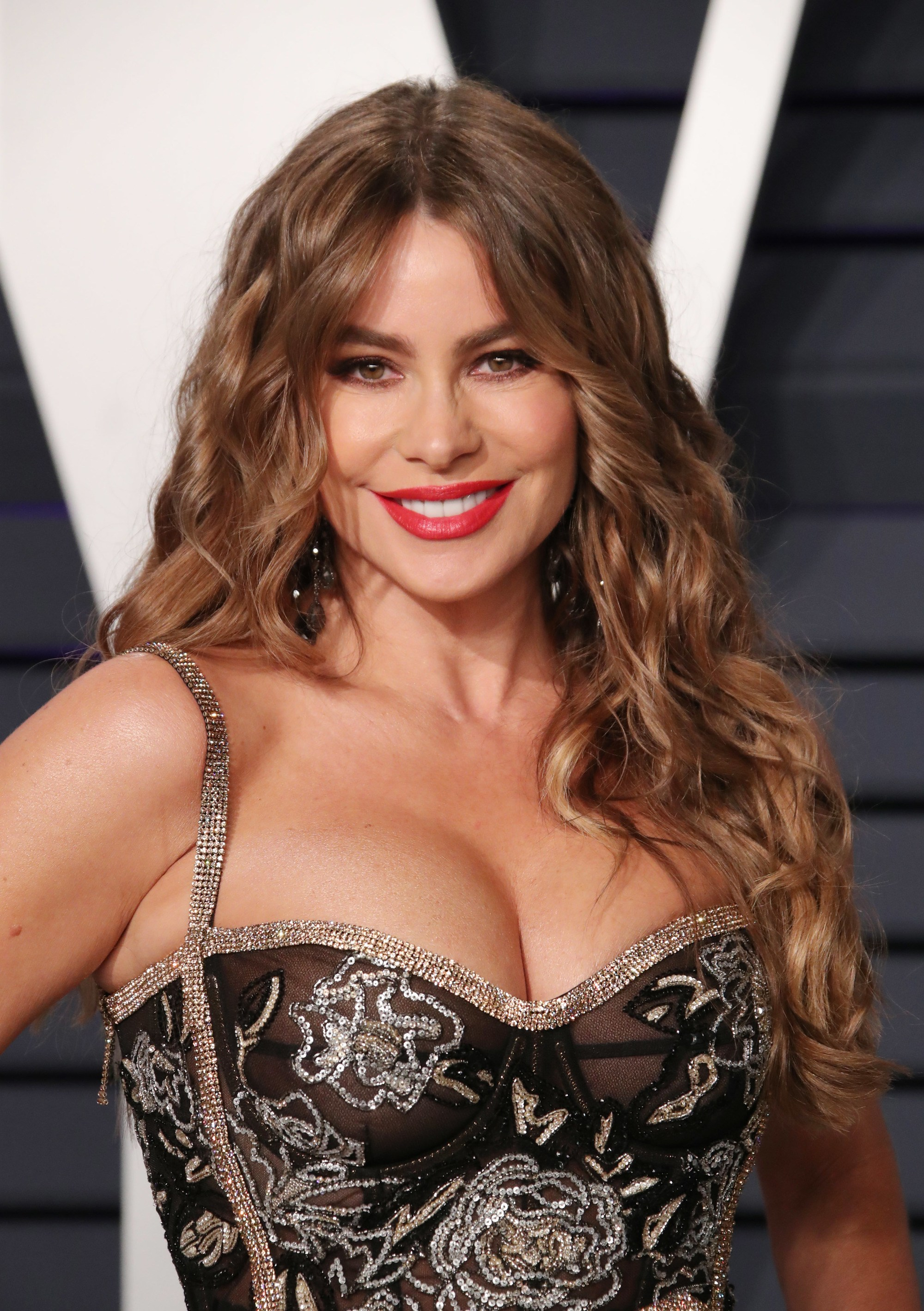 Sofia Vergara with long dulce de leche caramel hair styled into loose curls on the red carpet