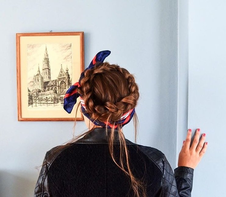Crown hair: Close up shot of a woman with chestnut brown hair styled into a crown braid, complete with a hair scarf accessory