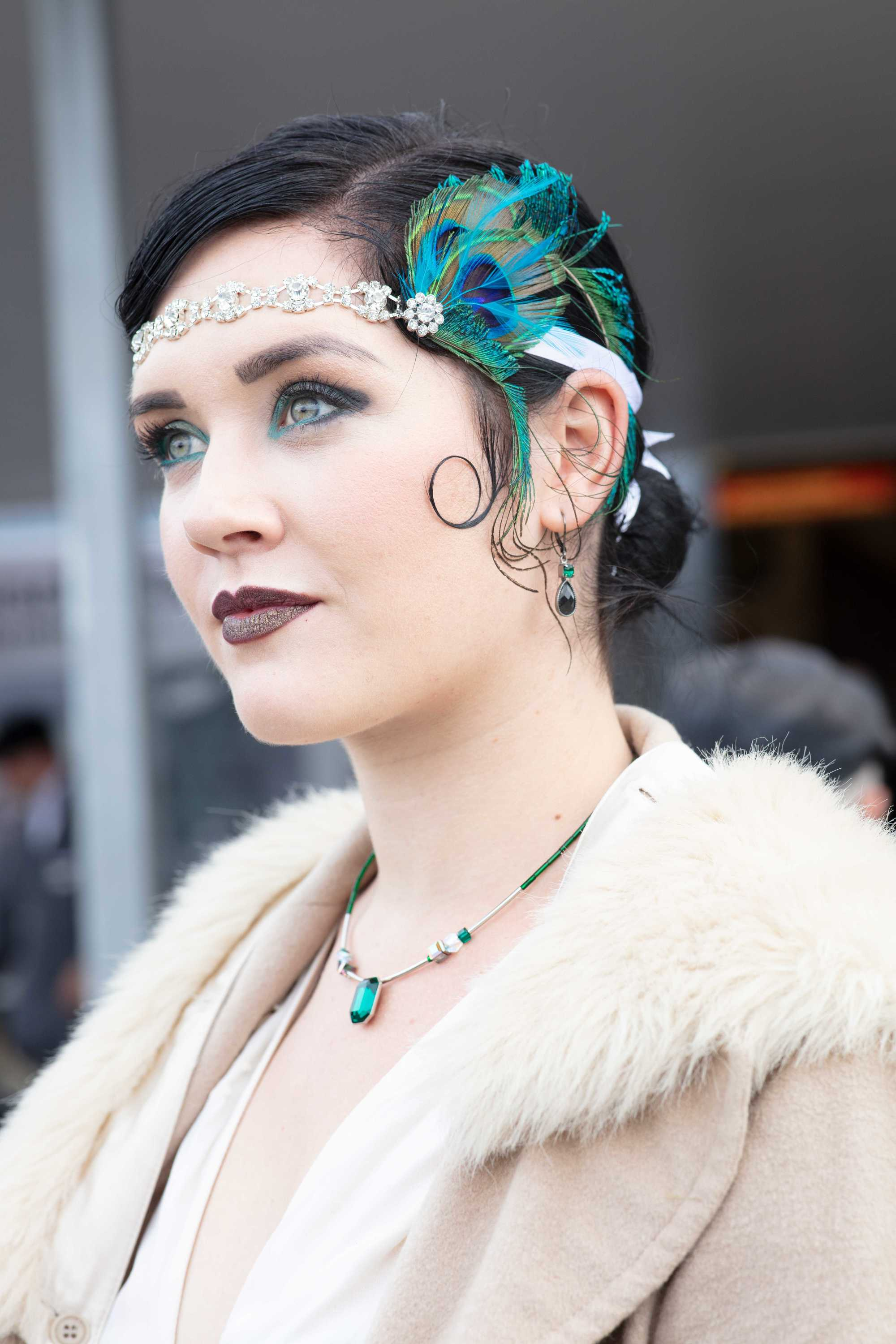 Flapper hairstyles for long hair: Woman at Goodwood Revival with dark brown hair in a low bun with a kiss curl and peacock feather headband