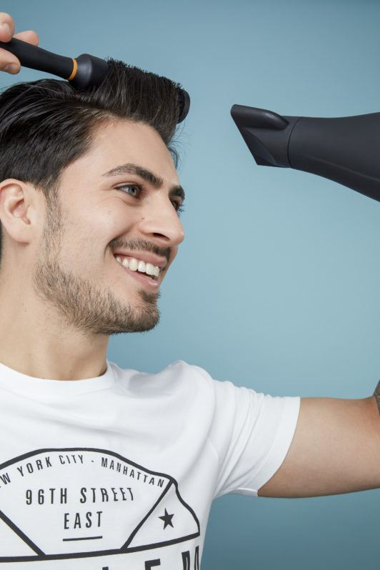 How to blow dry men's hair: Brown haired man using a round brush to blow dry his hair, wearing a white t-shirt