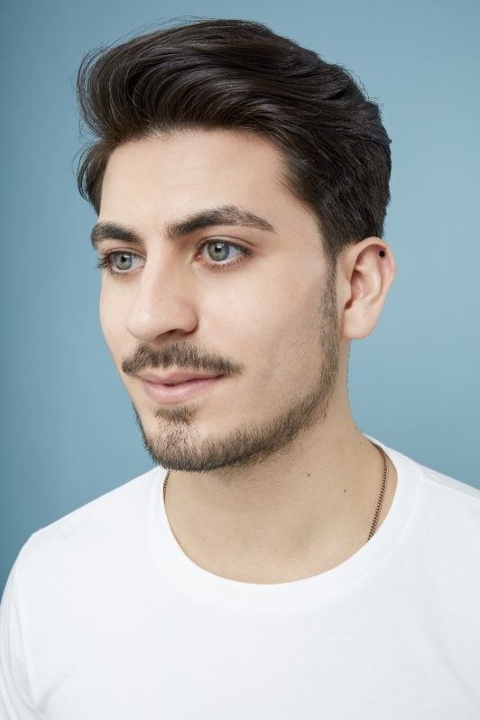 How to blow dry men's hair: Close up shot of a brunette man with swept over hair and facial hair wearing a white tshirt