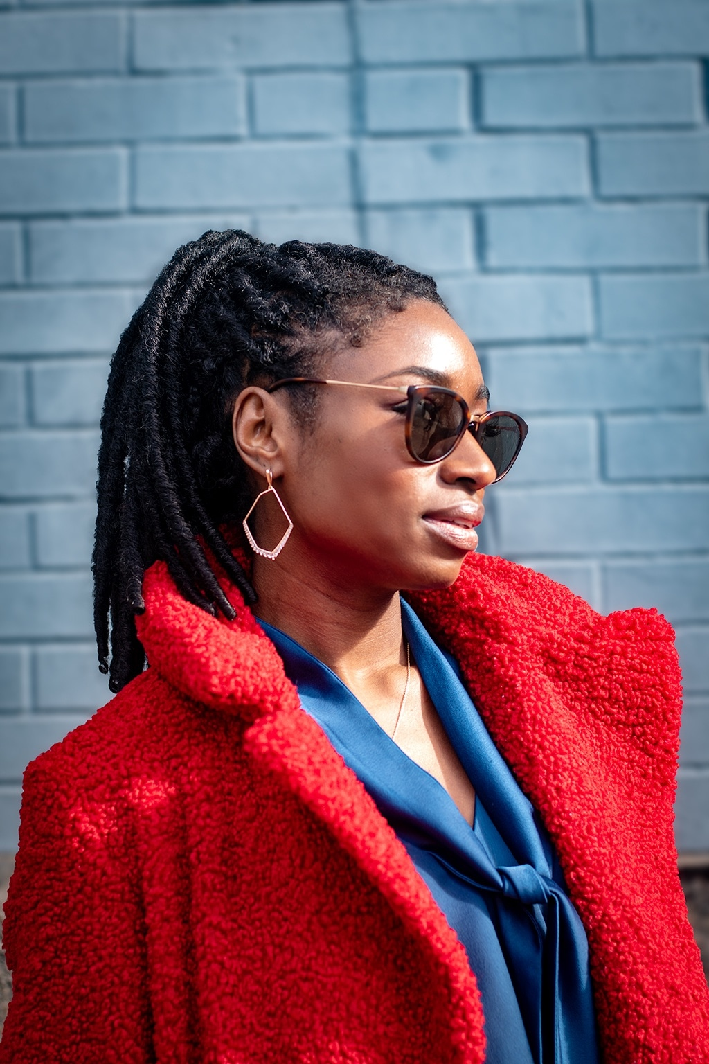 NYFW AW19 Street Style: Woman with dark brown faux locs styled into a high ponytail, wearing sunglasses with ted coat and blue blouse underneath