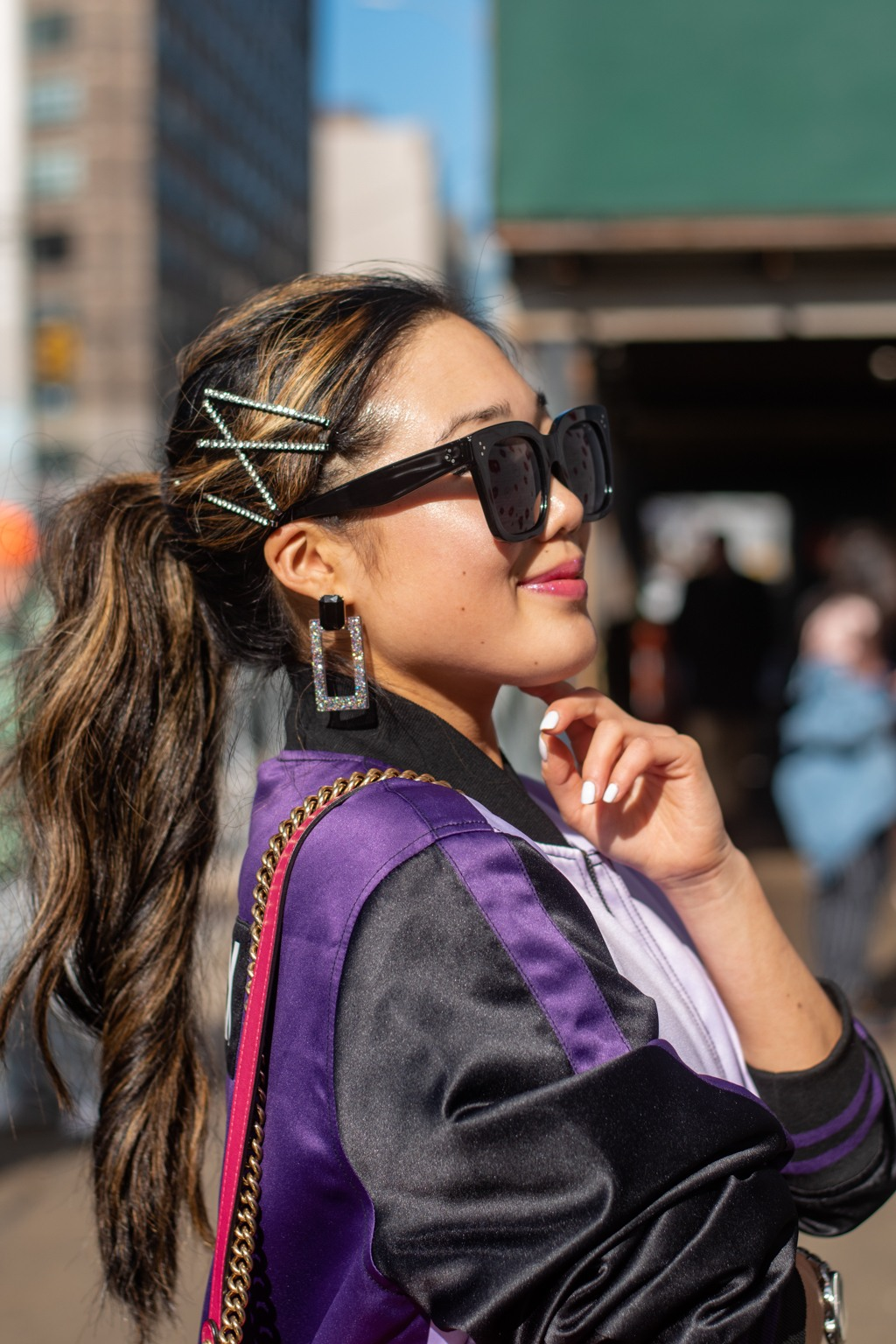 NYFW AW19 Street Style: Shot of woman with dark brown hair with caramel brown highlights wearing diamante hair slides, with square earrings with sunglasses