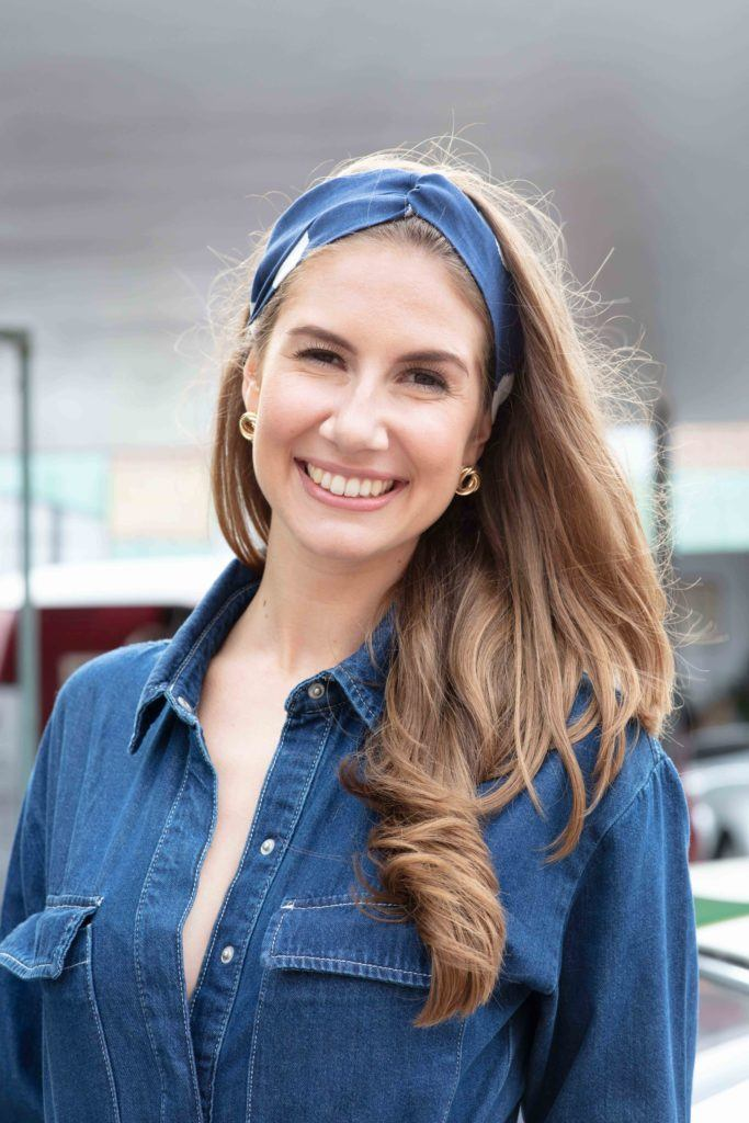 Vintage hairstyles for long hair: Close up shot of a woman with long light brown hair styled into loose waves and tied with a head wrap accessory, wearing a denim outfit at Goodwood festival