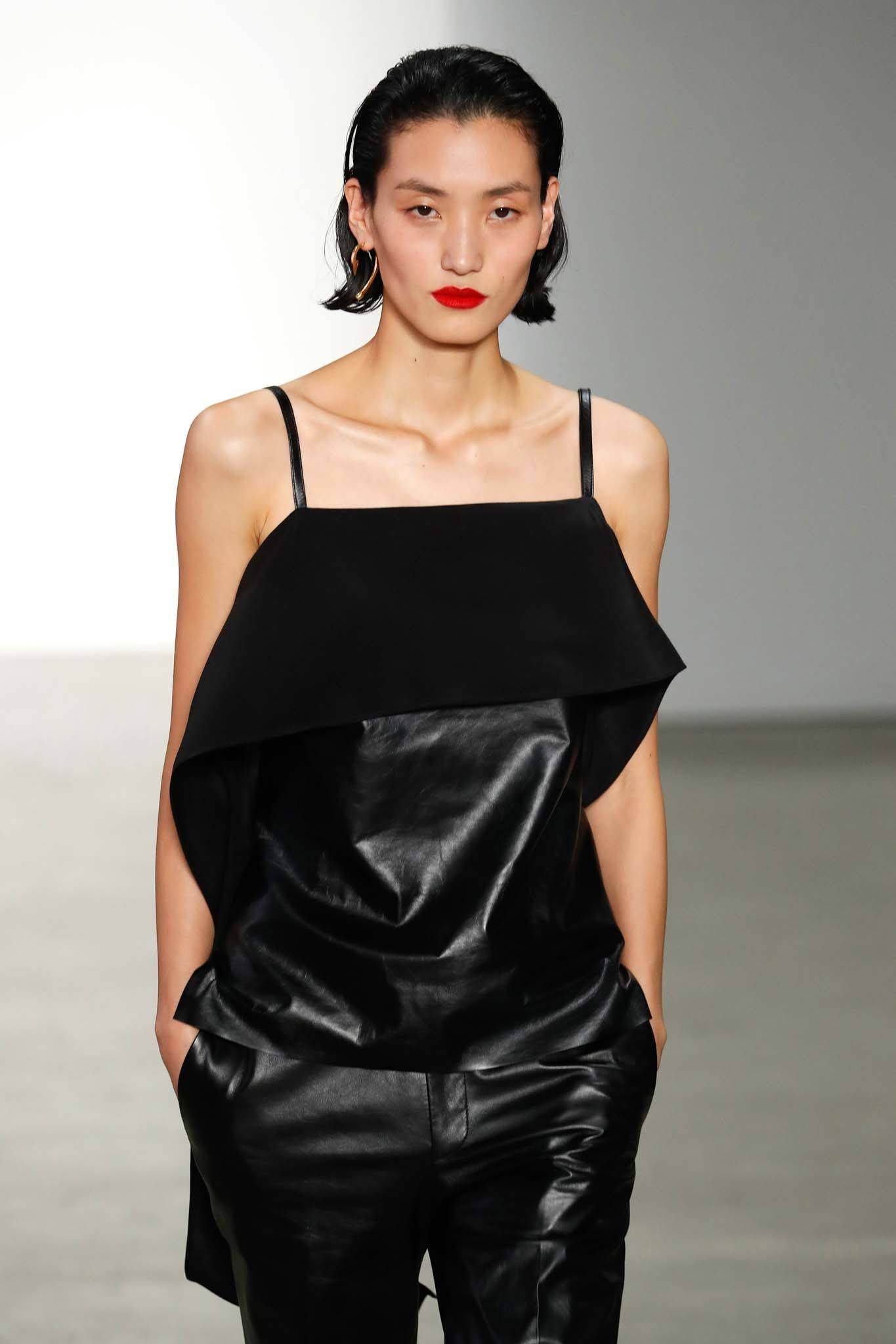 NYFW Catwalk Trends: Woman on Helmut Lang FW19 show with short dark brown bob swept back wearing all black outfit and red lipstick.