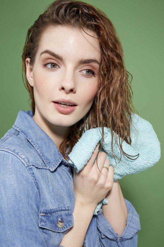 How to scrunch hair tutorial: Close up of a woman with curly brown hair which she is drying with a blue microfibre towel