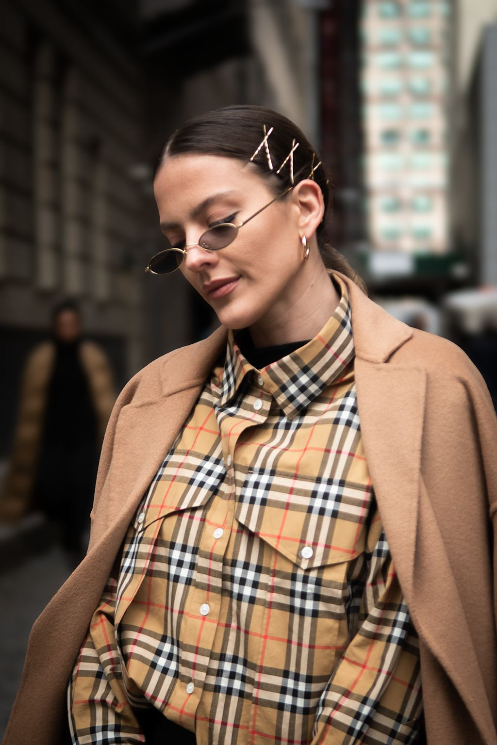 Shot of a woman with dark brown low sleek ponytail with criss cross bobby pins, wearing plaid print shirt with beige coat and mini sunglasses