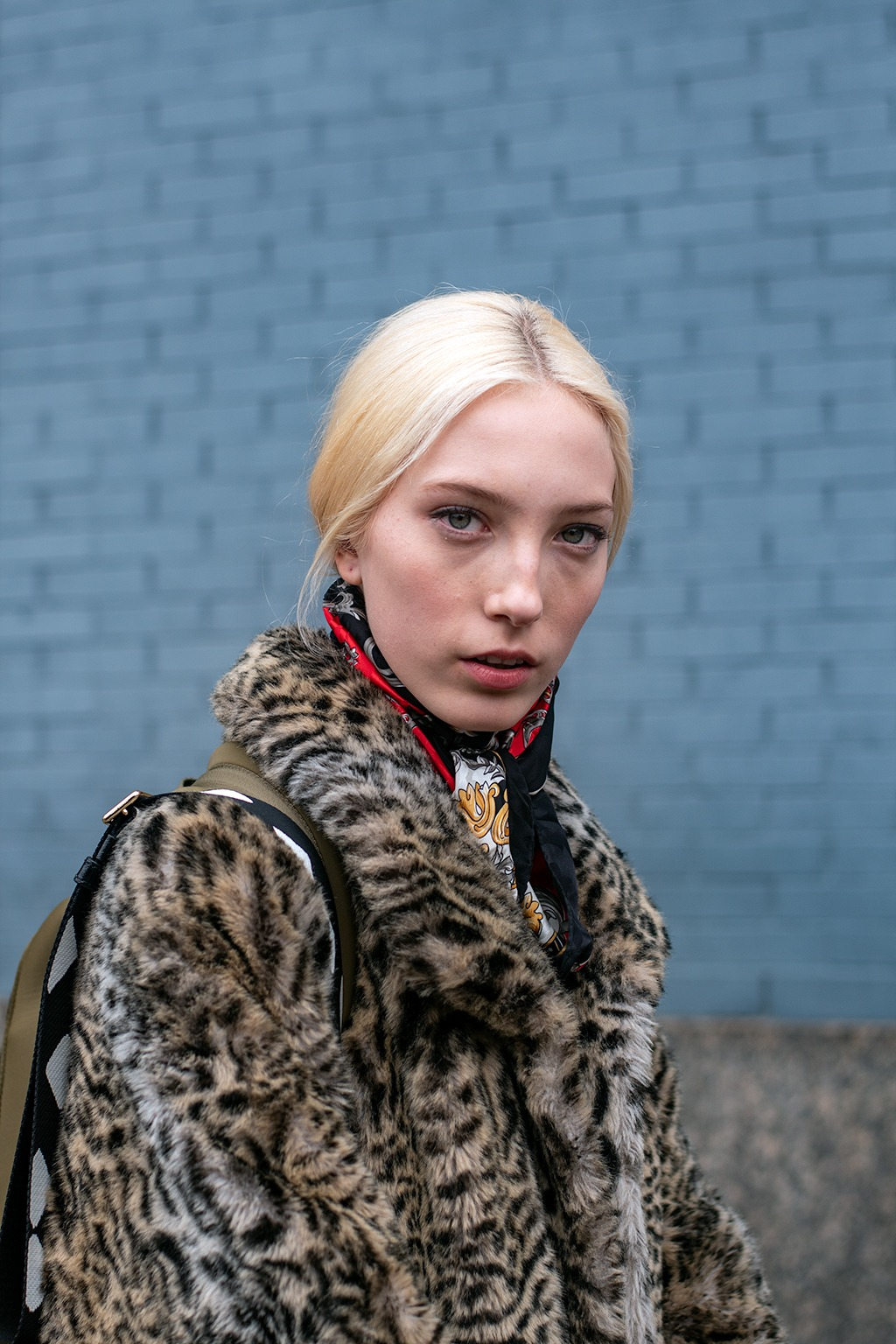 NYFW AW19 Street Style: Shot of a woman with platinum blonde hair with sleek middle part with wispy hair trends, wearing a leopard print jacket with a chain print neckerchief